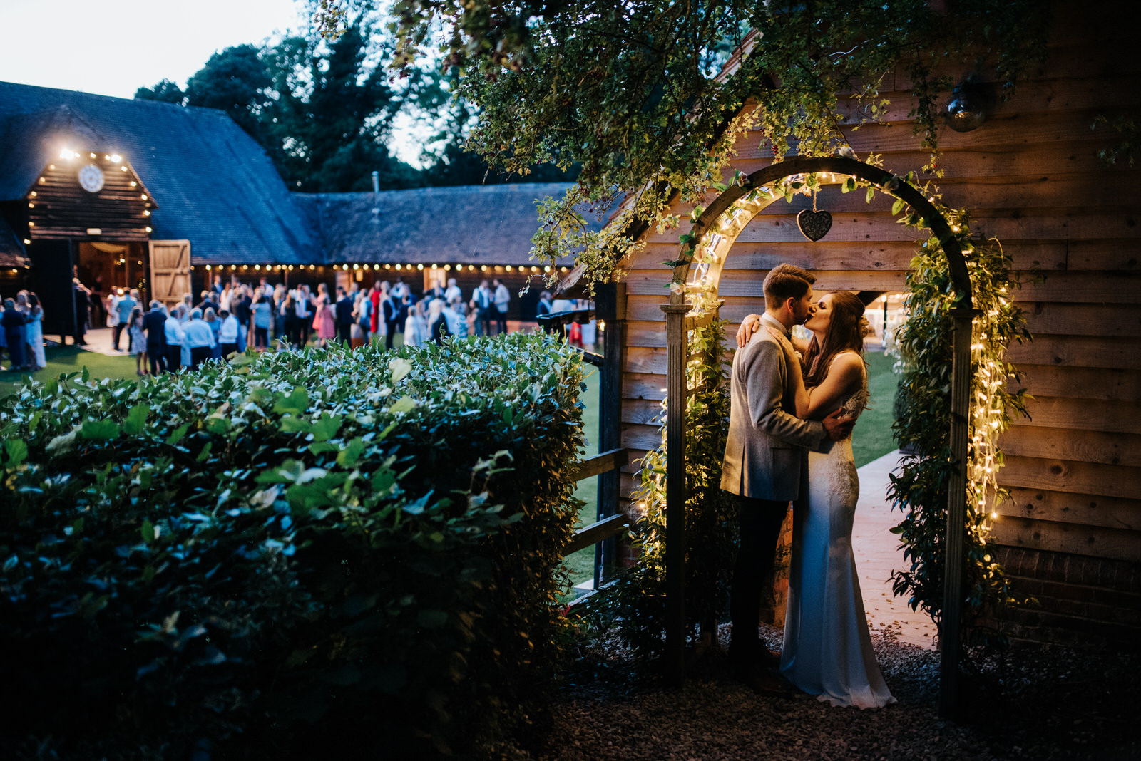Bride and groom kiss under fairy lights as guests enjoy the even