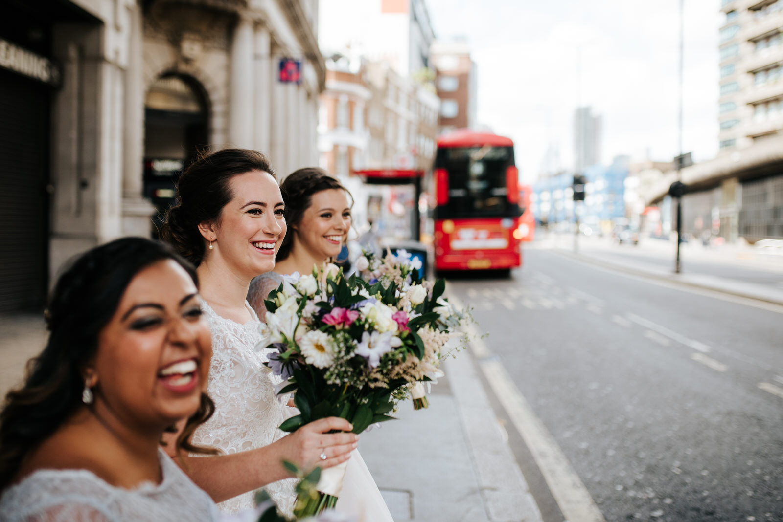 Bride and bridesmaids wait to cross the road in London to arrive