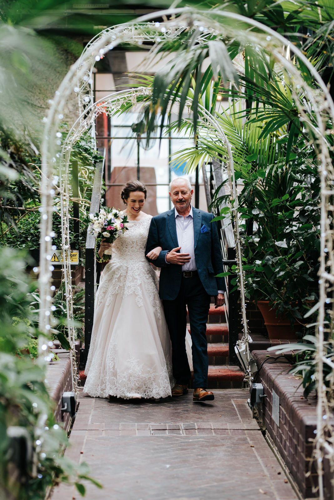 Bride and her uncle walk through lush greener and approach the a