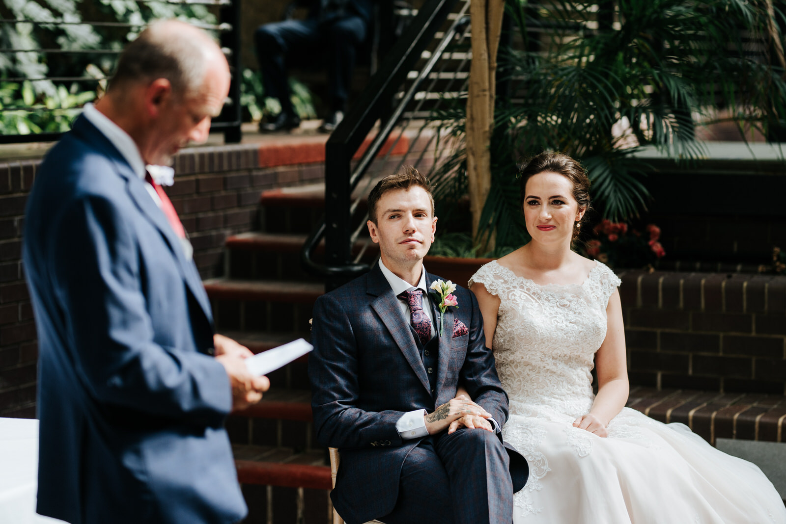 Bride and groom look at father of the groom as he makes emotiona