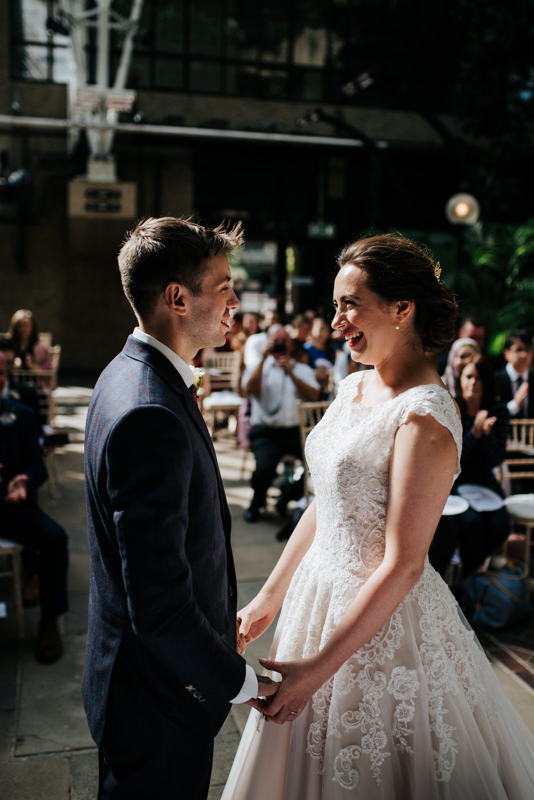 Bride and groom hold hands and smile at each other seconds after