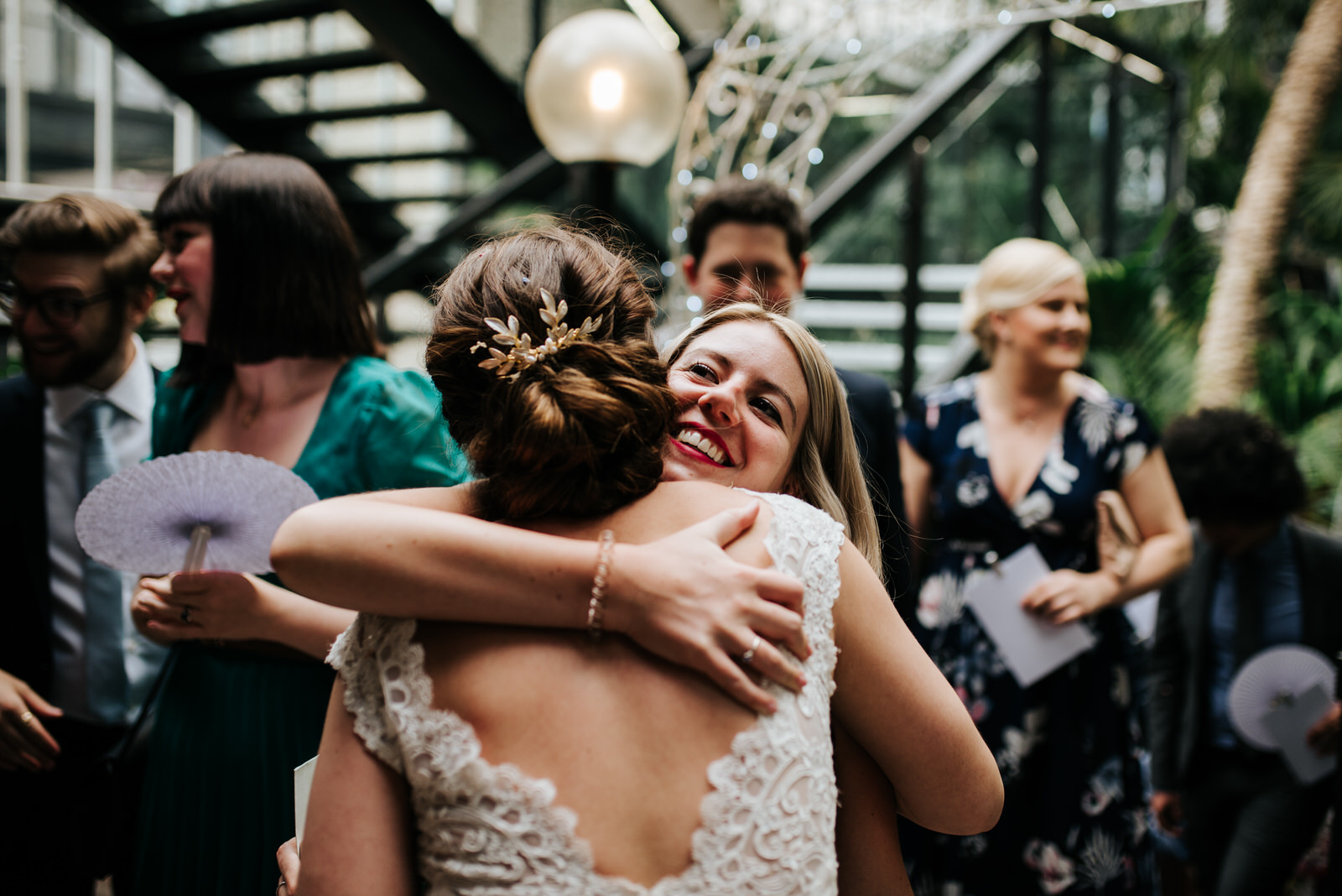 Bride and close friend hug each other and smile after wedding ce