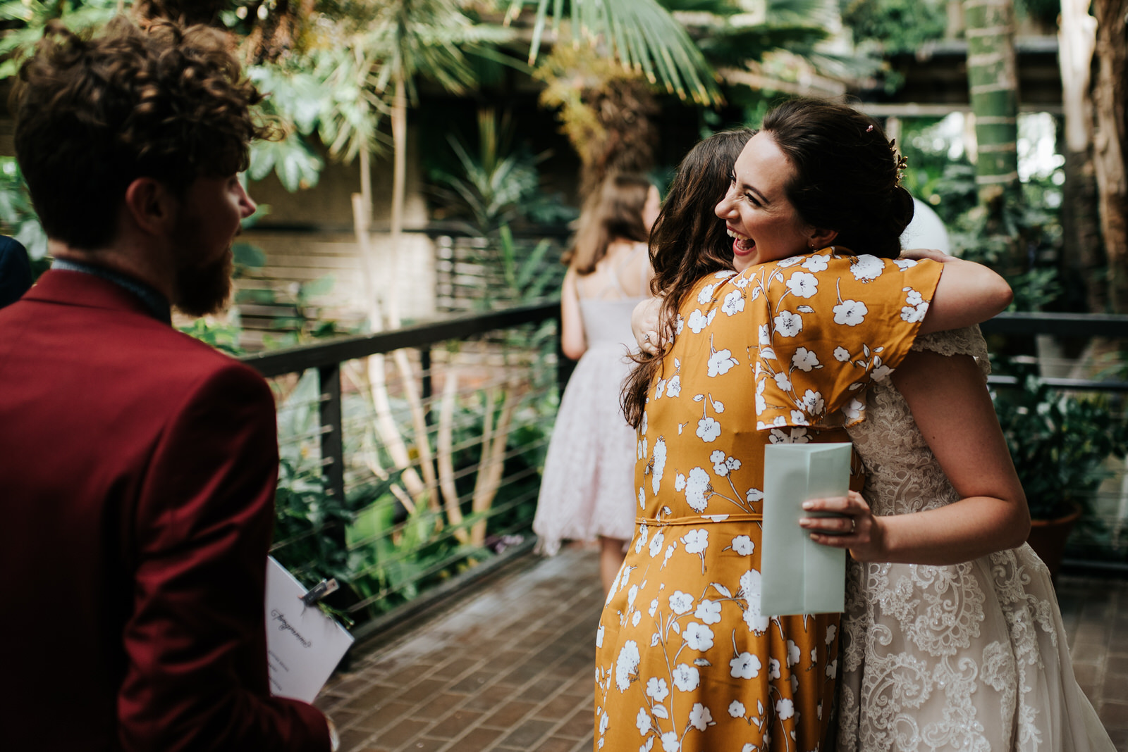 Bride hugs another friend while smiling with her teeth in close