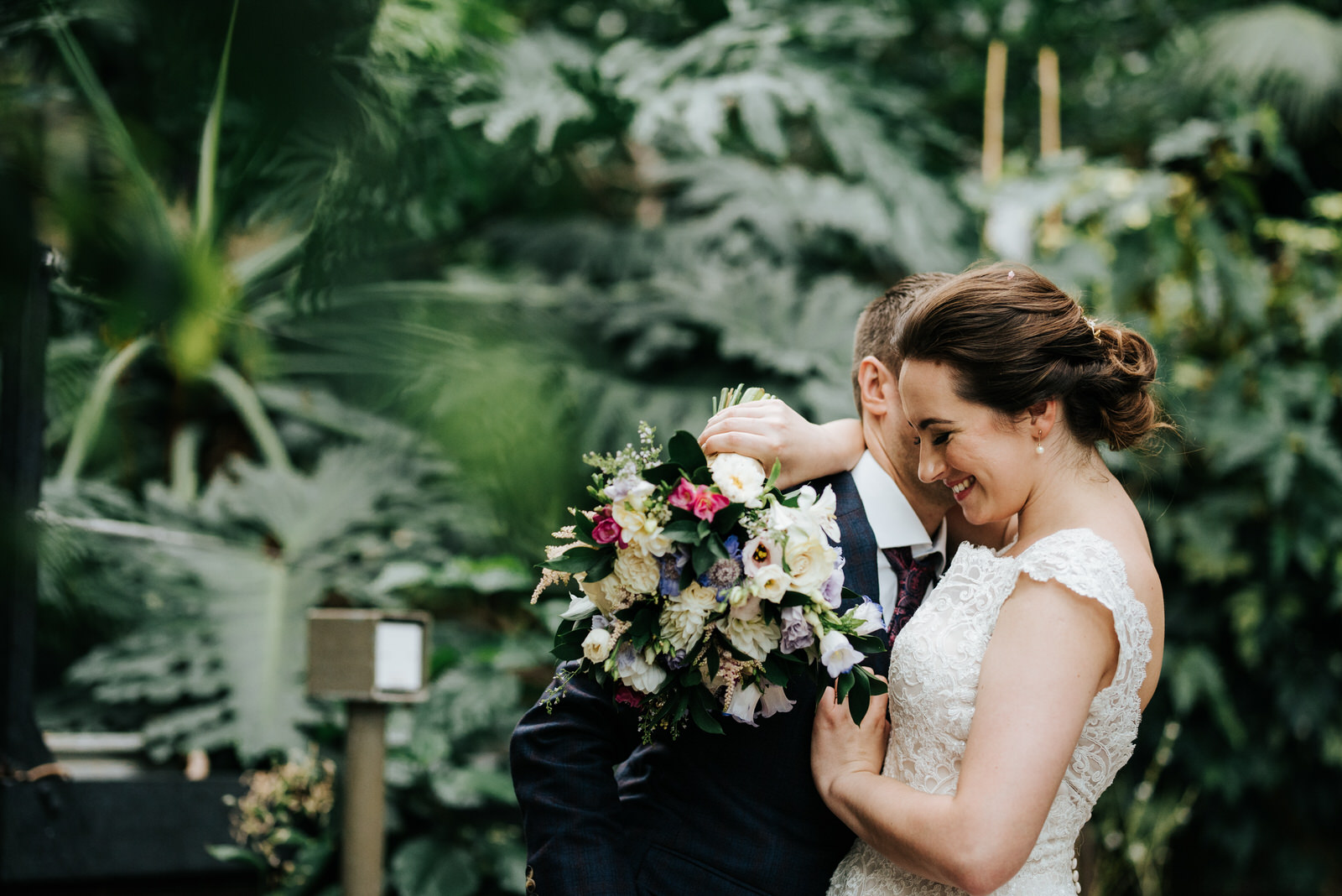 Groom whispers into brides ear as she smiles while hugging him w