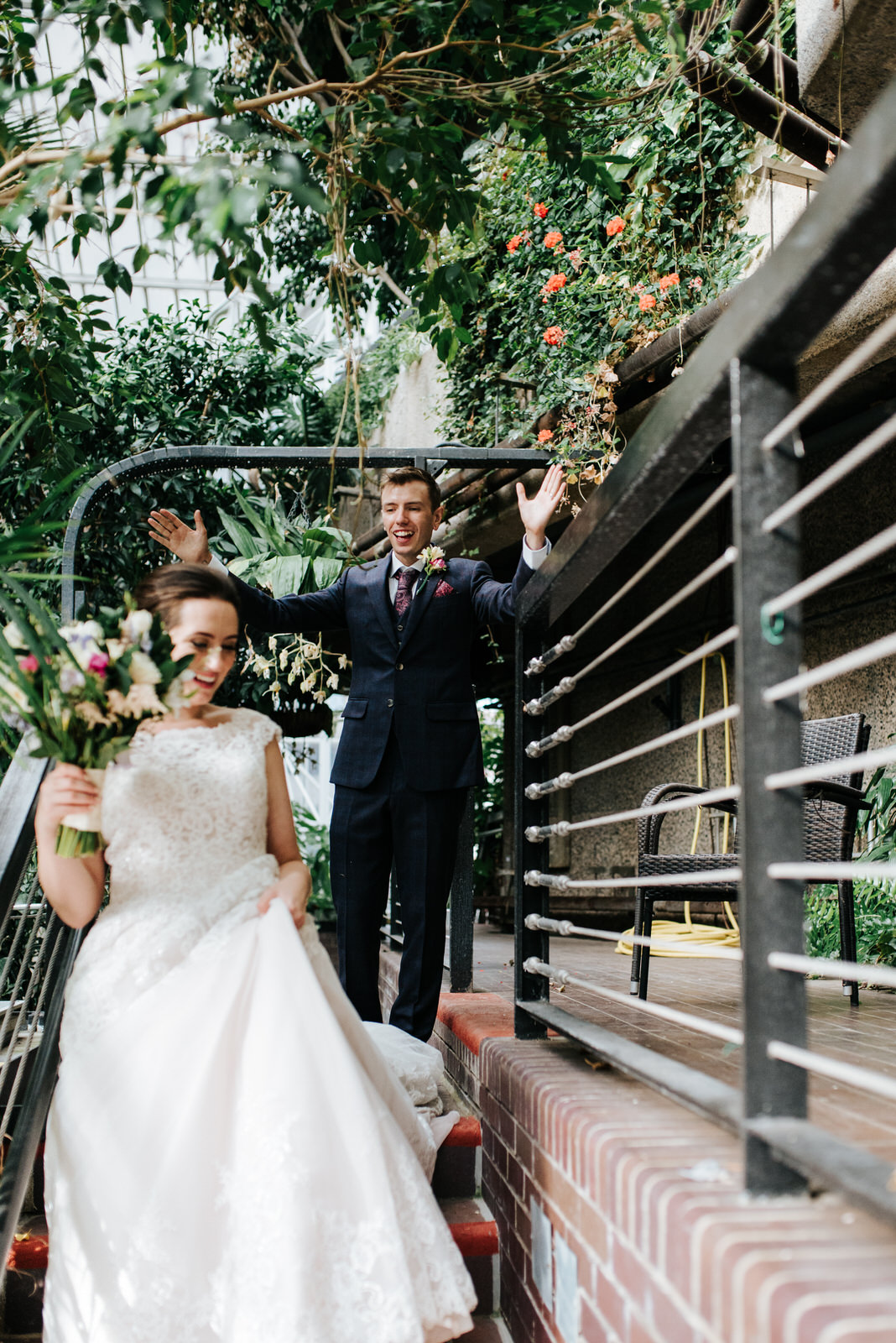 Bride walks down stairs in Barbican Centre as groom cheers from