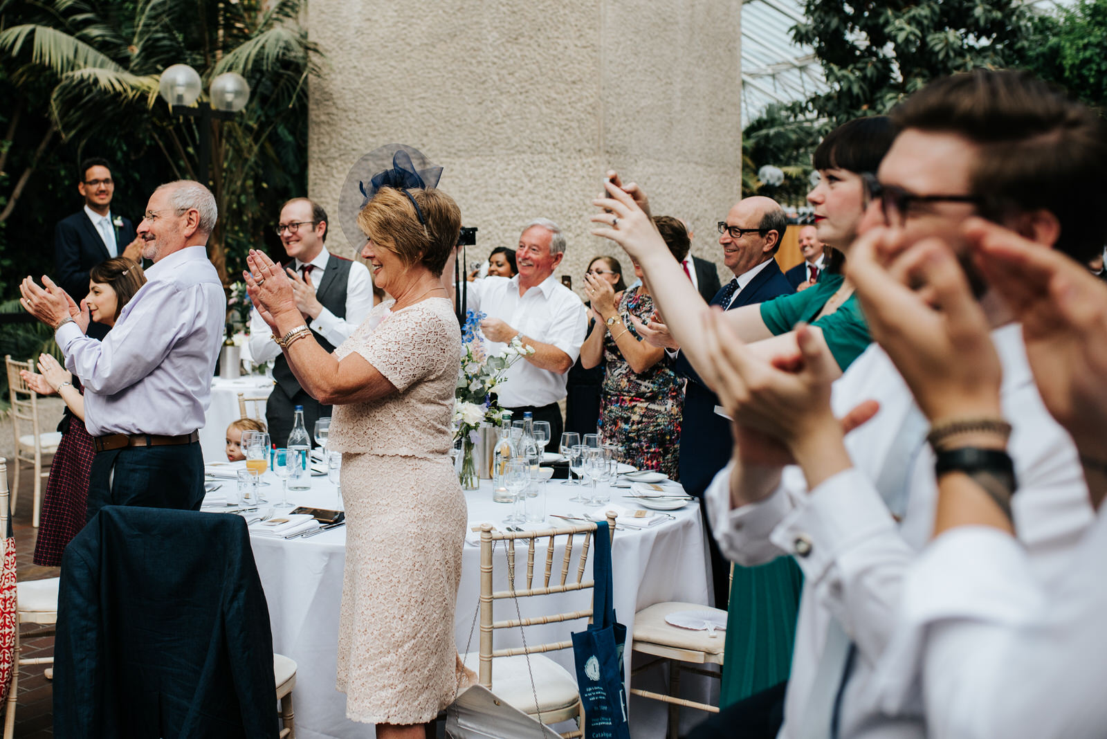 Guests clap and take photos as bride and groom enter wedding bre