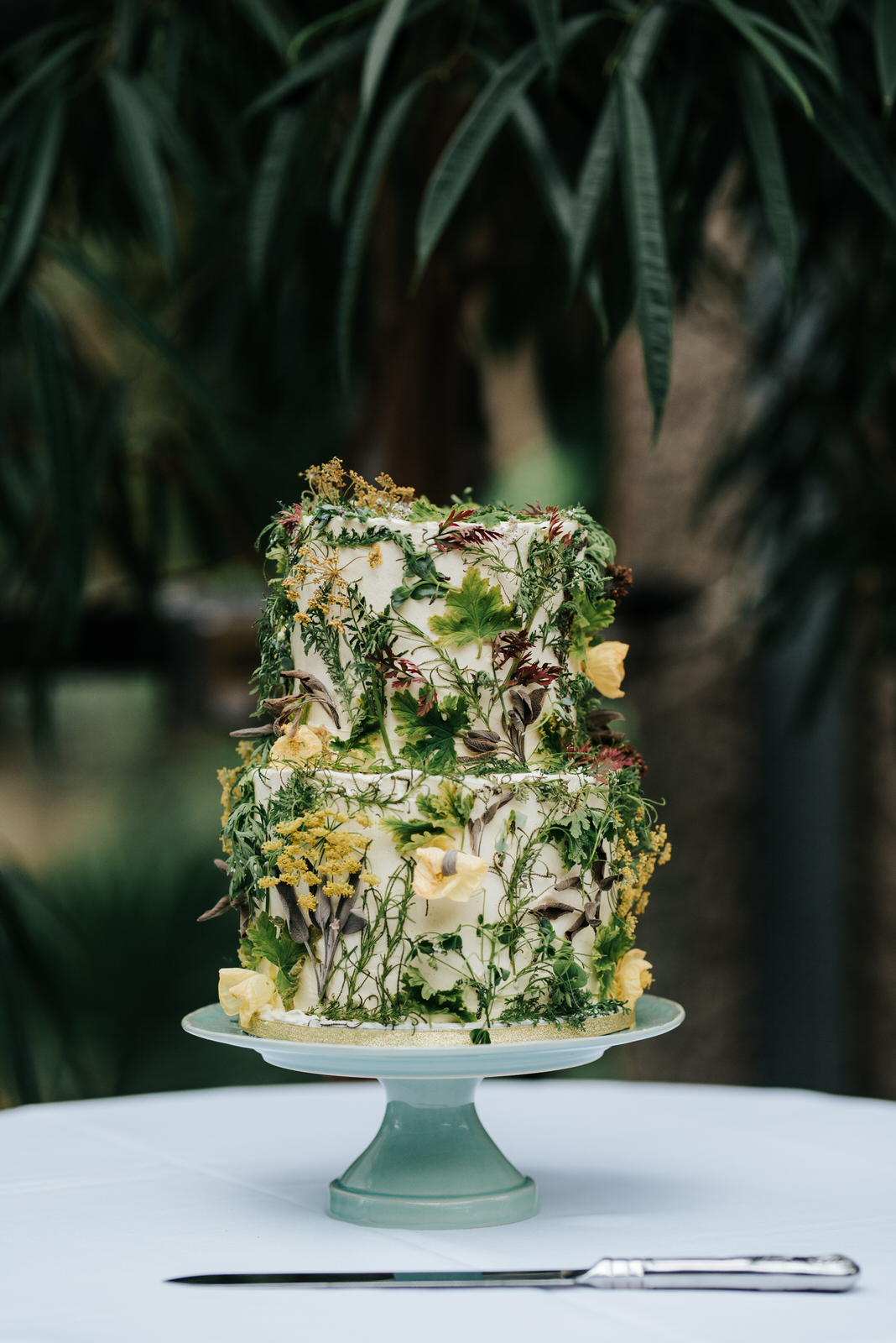 Detail photograph of stunning wedding cake decorated with shrubs