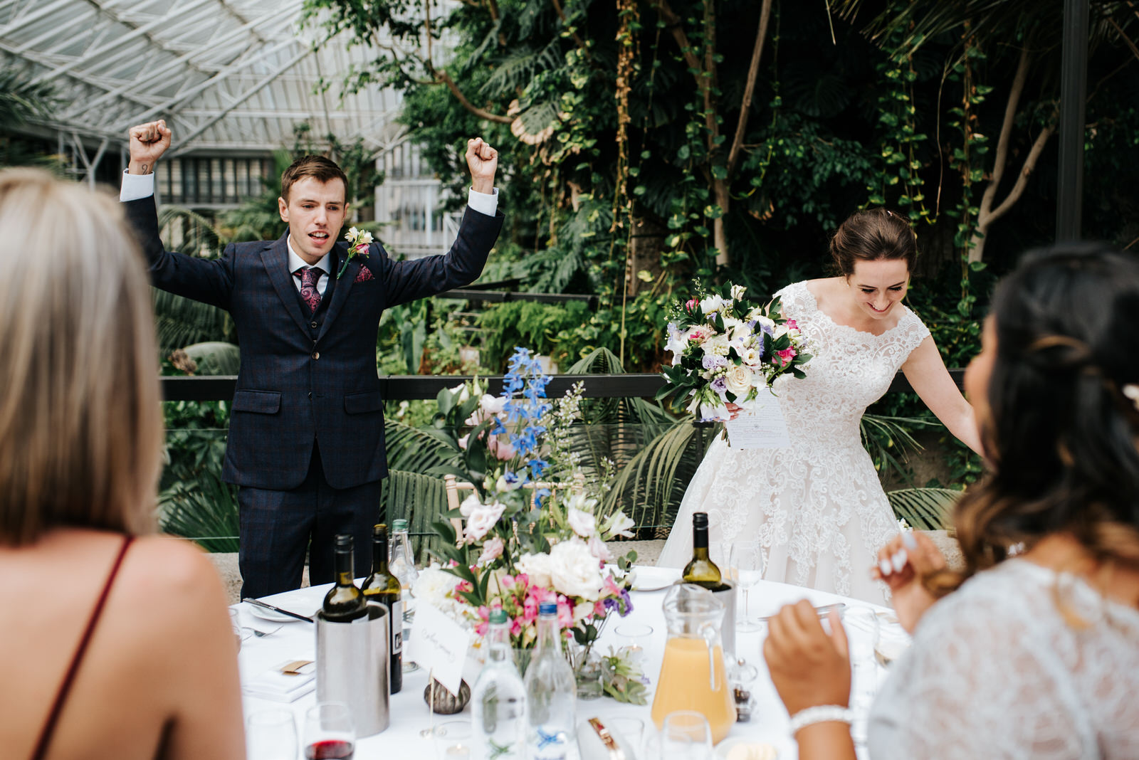 Groom cheers as he and his wife arrive at their table in order to sit down