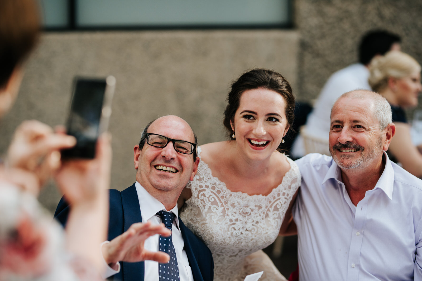 Bride and two family members smile into phone camera as they are photographed