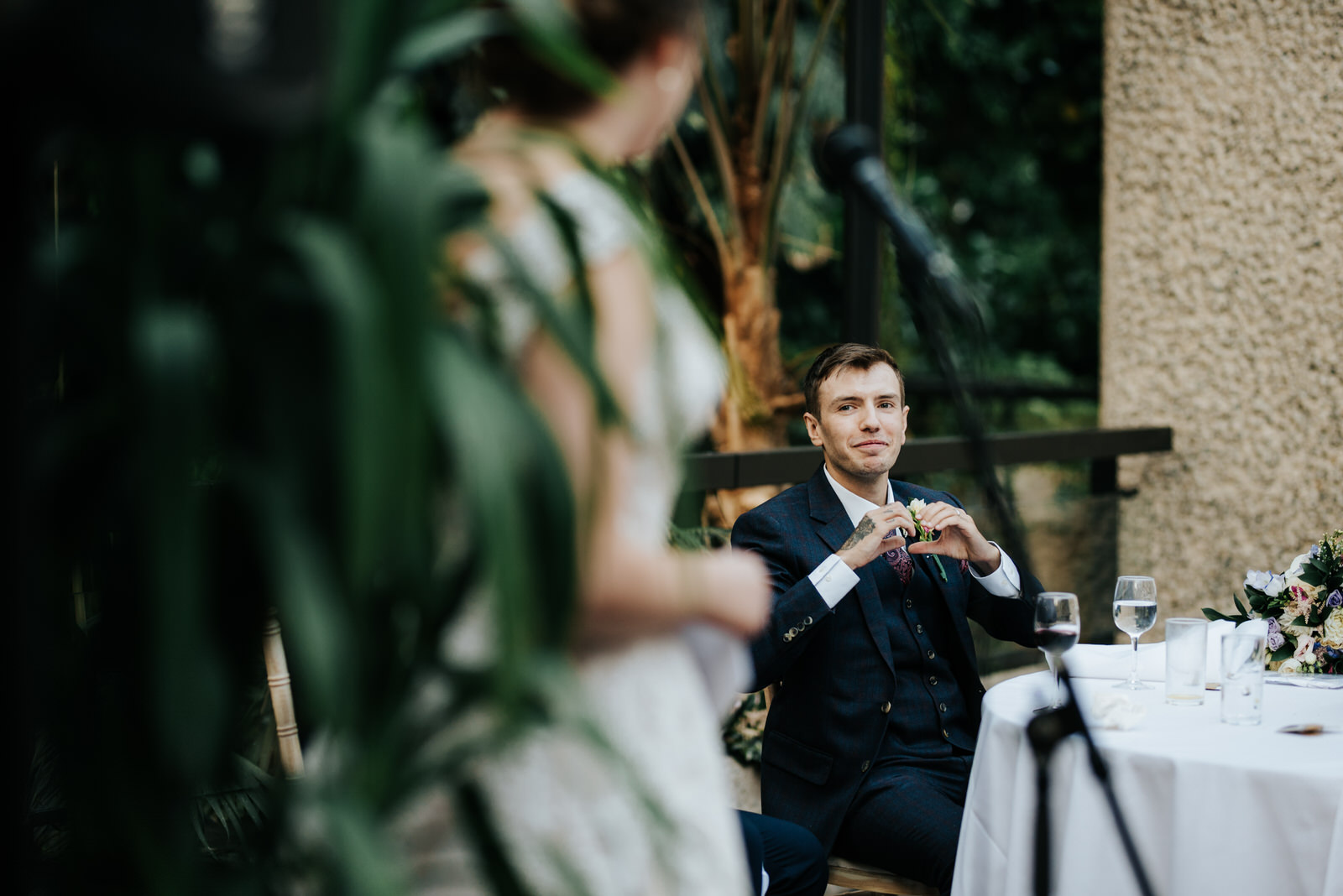 Groom looks towards bride with a heart formed with his hands aft