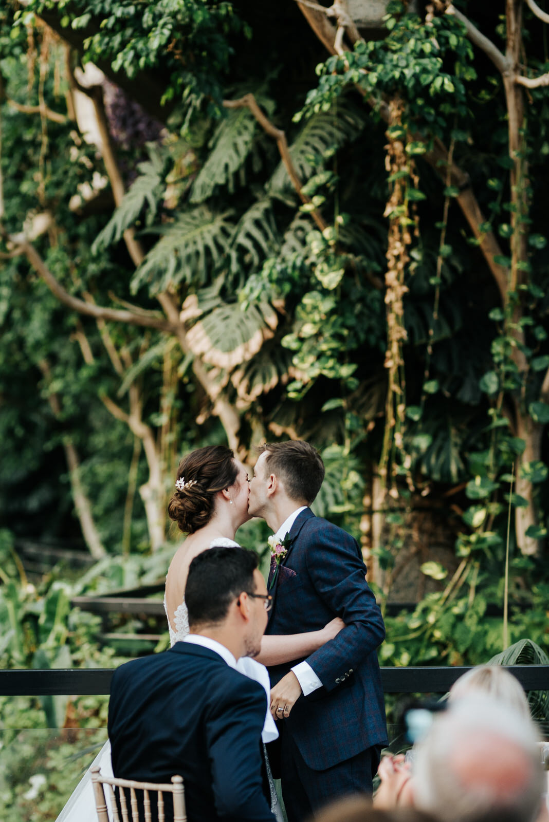 Groom kisses bride on the cheek while gorgeous greenery can be s