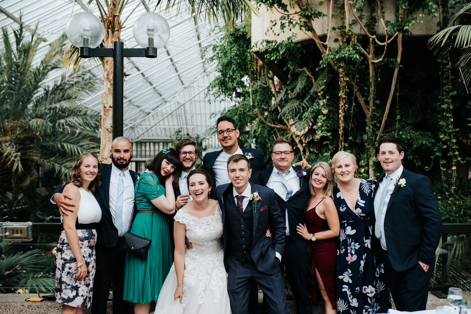 Posed group photograph of bride, groom and a variety of friends