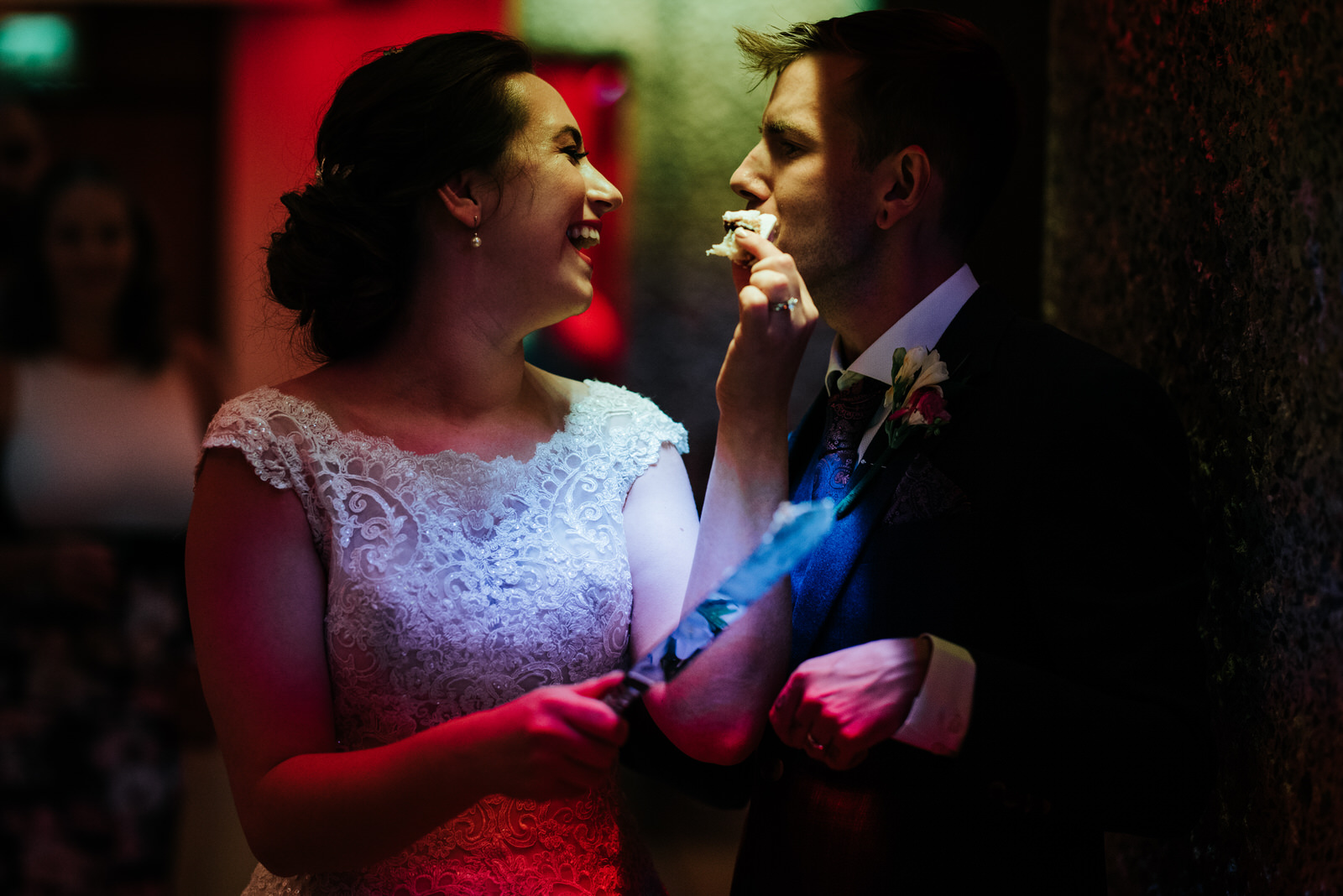 Bride and groom feed each other a slice of cake under funky, art