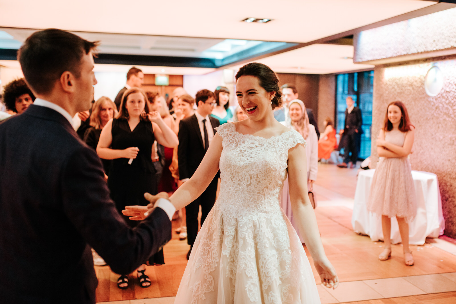 Bride smiles as she and groom begin their first dance