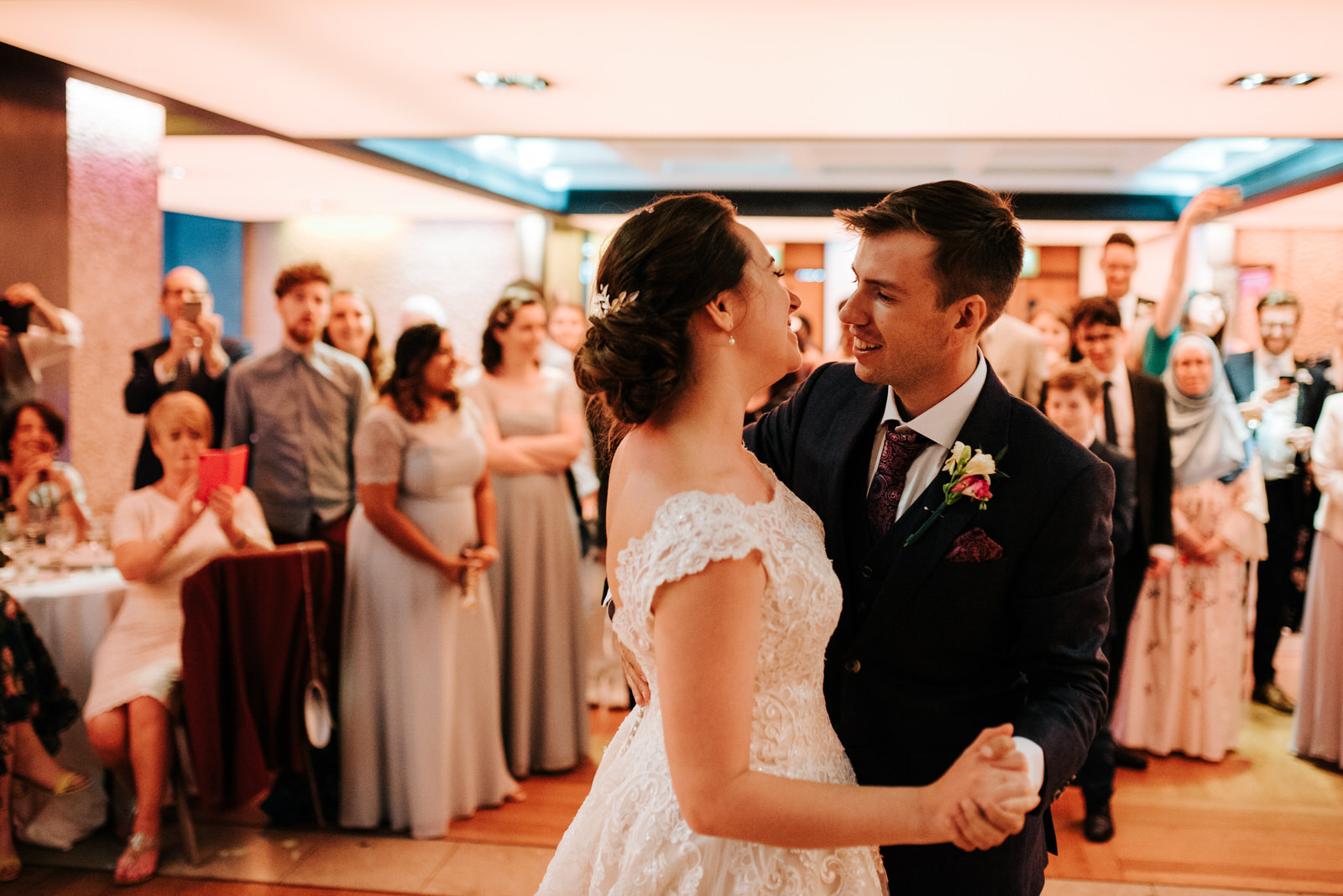 Bride and groom do their first dance as guests smile from behind