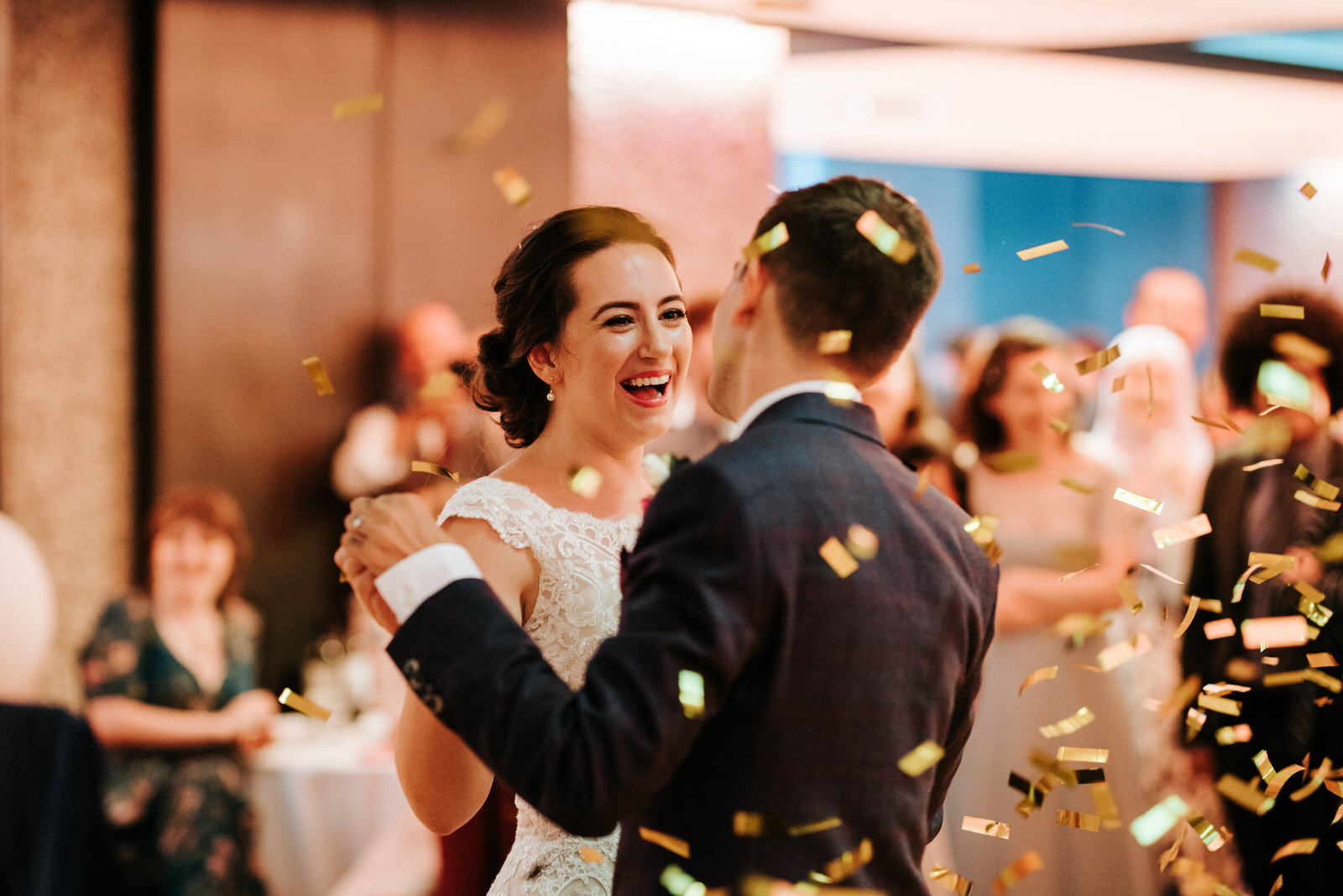 Bride smiles at groom as confetti falls during the end of their