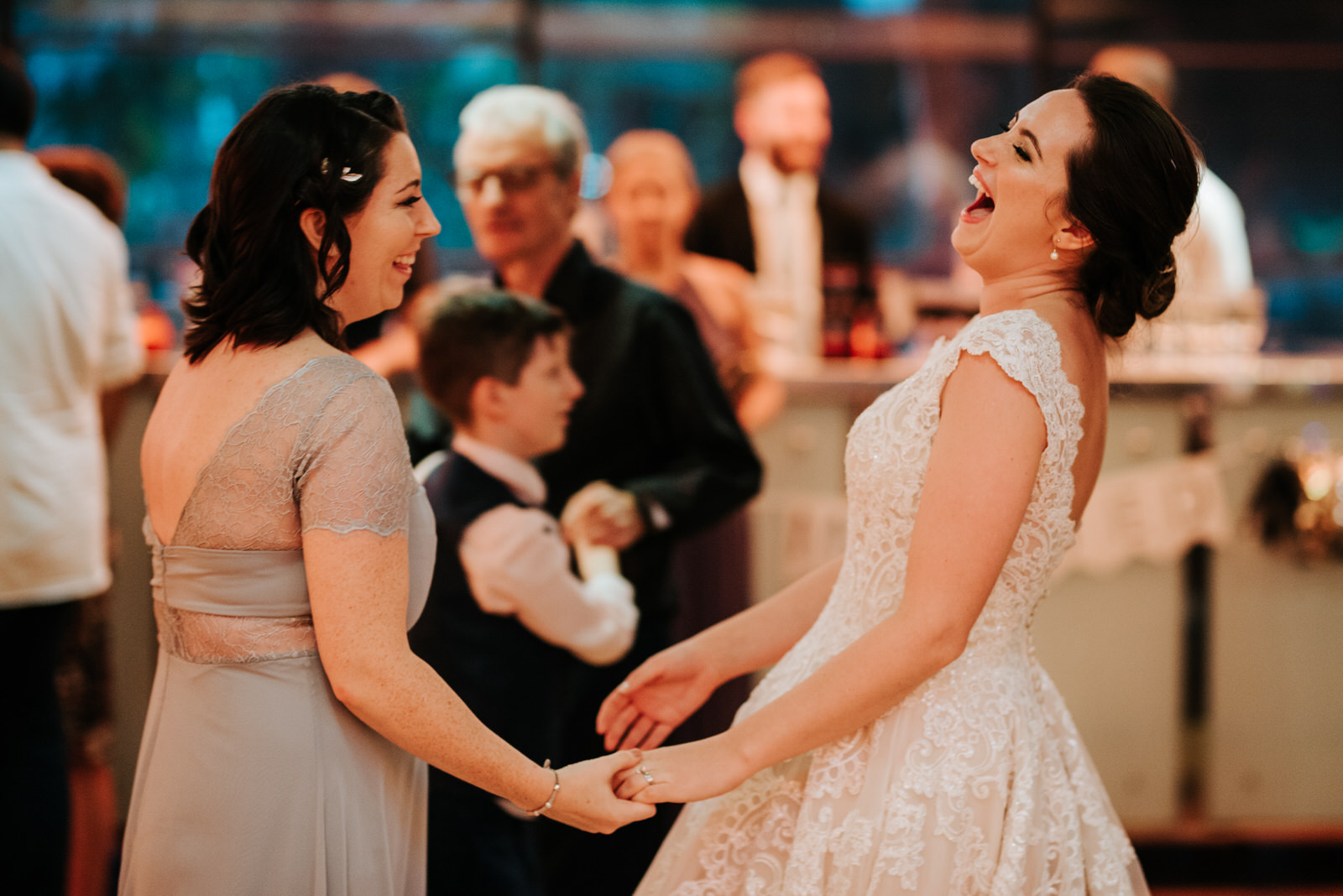Bride and close friend share a laugh while dancing