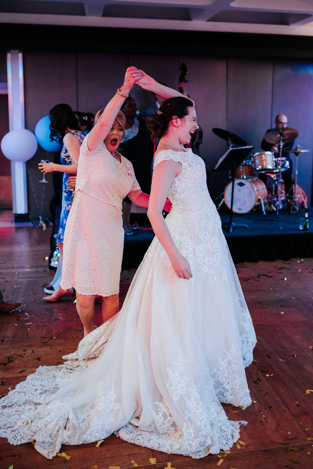 Bride laughs loudly as her auntie makes her do a twirl on the da