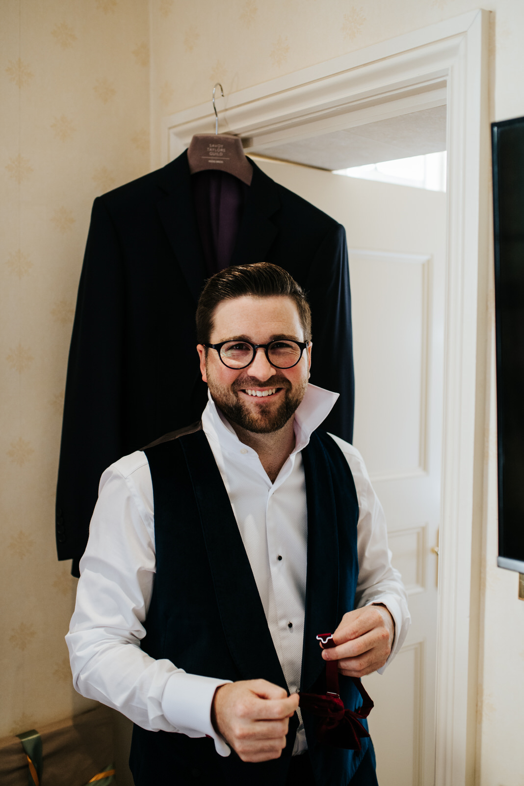 Groom smiles at camera as he buttons up his shirt