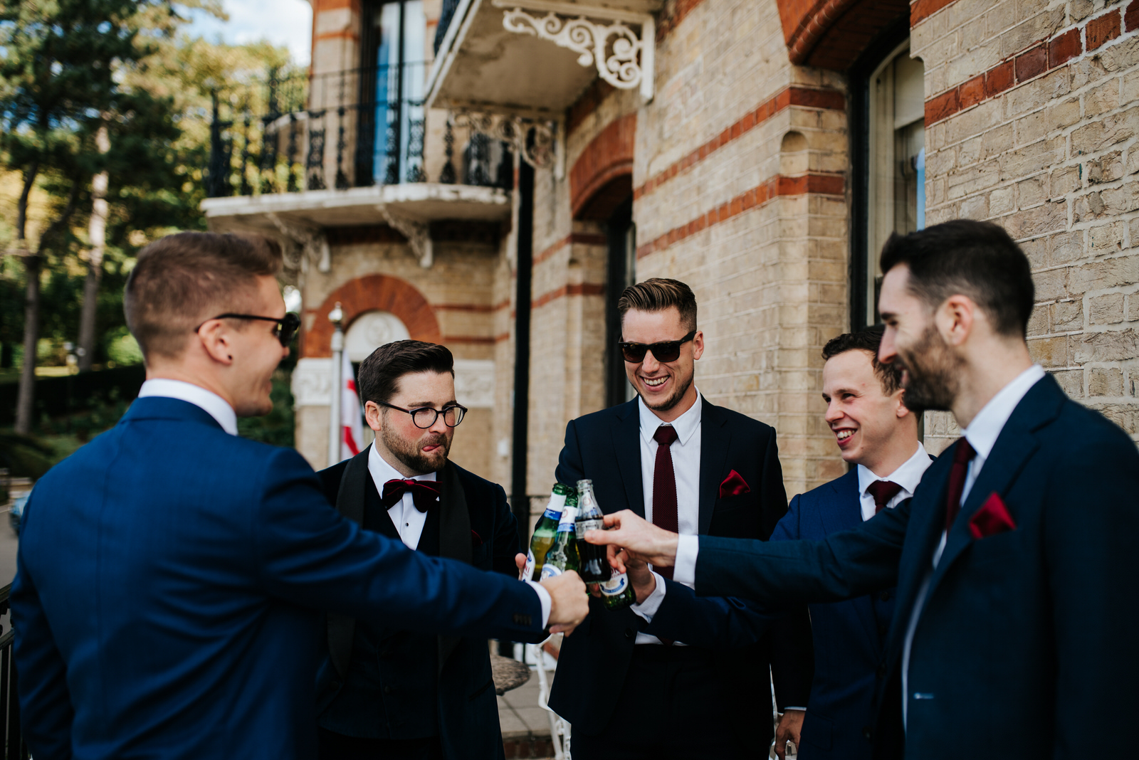Group shot of groomsmen as they have a drink and toast before ceremony