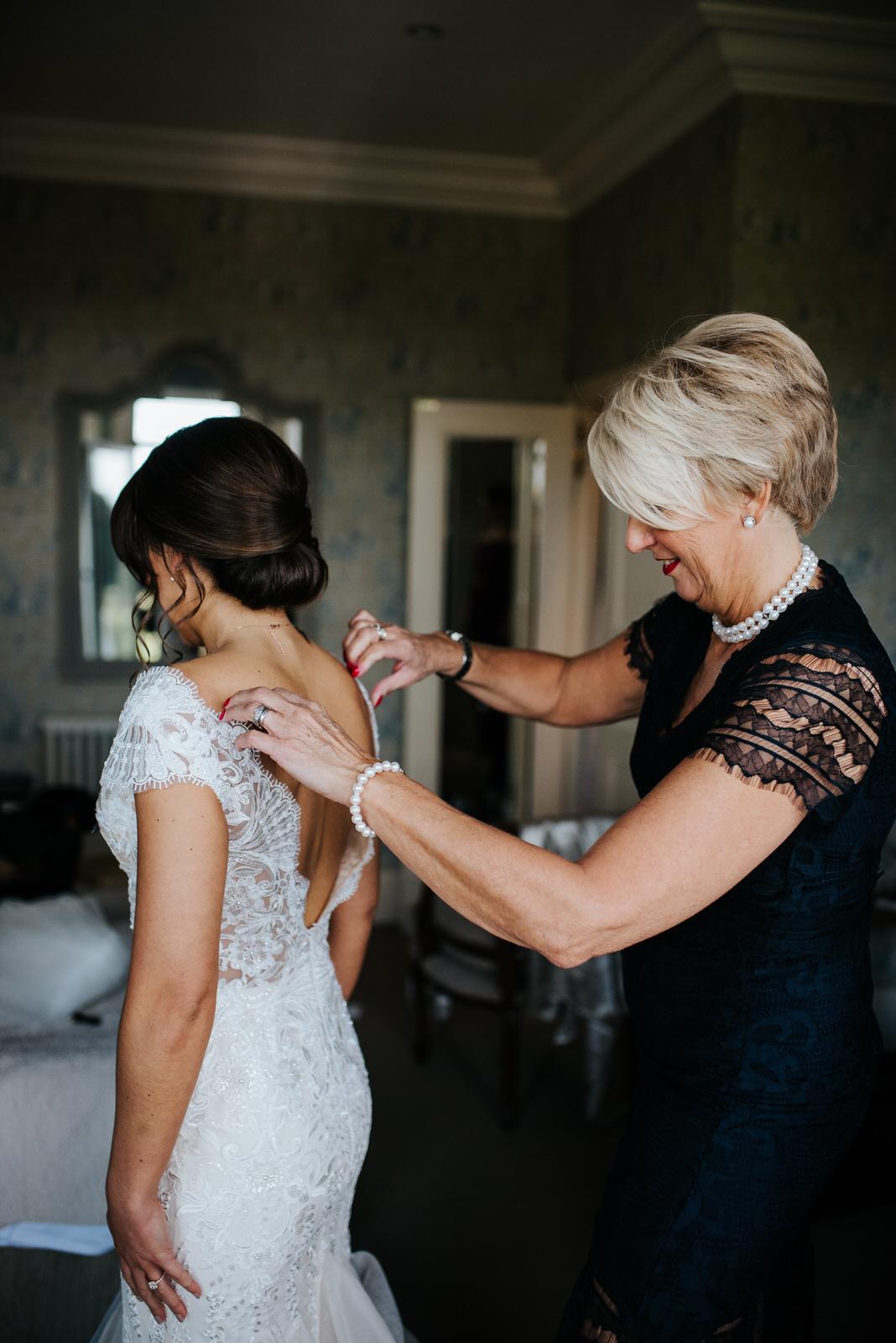 Bride's mom helps bride put on wedding dress
