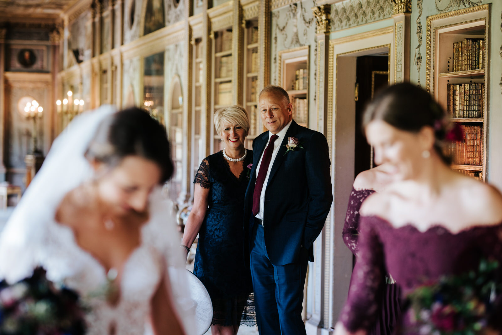 Bride's mum and step-dad look lovingly at bride and admire her