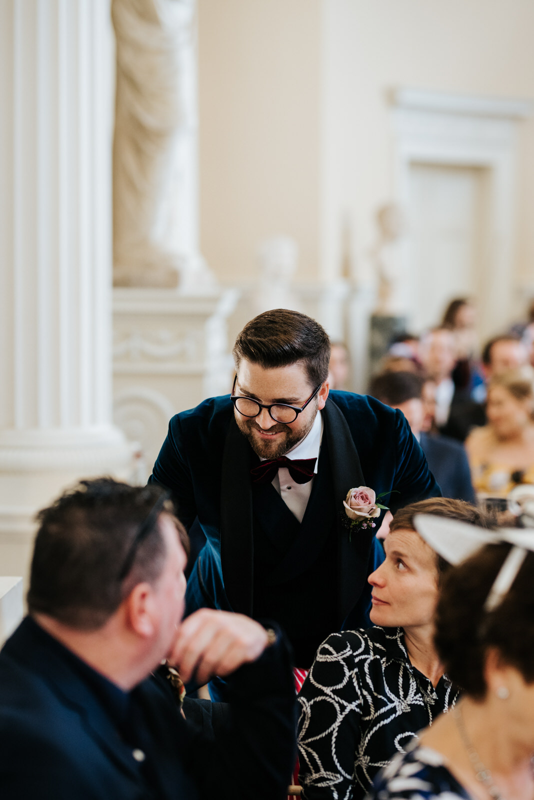 Groom chats to guests as he waits for wedding ceremony to begin