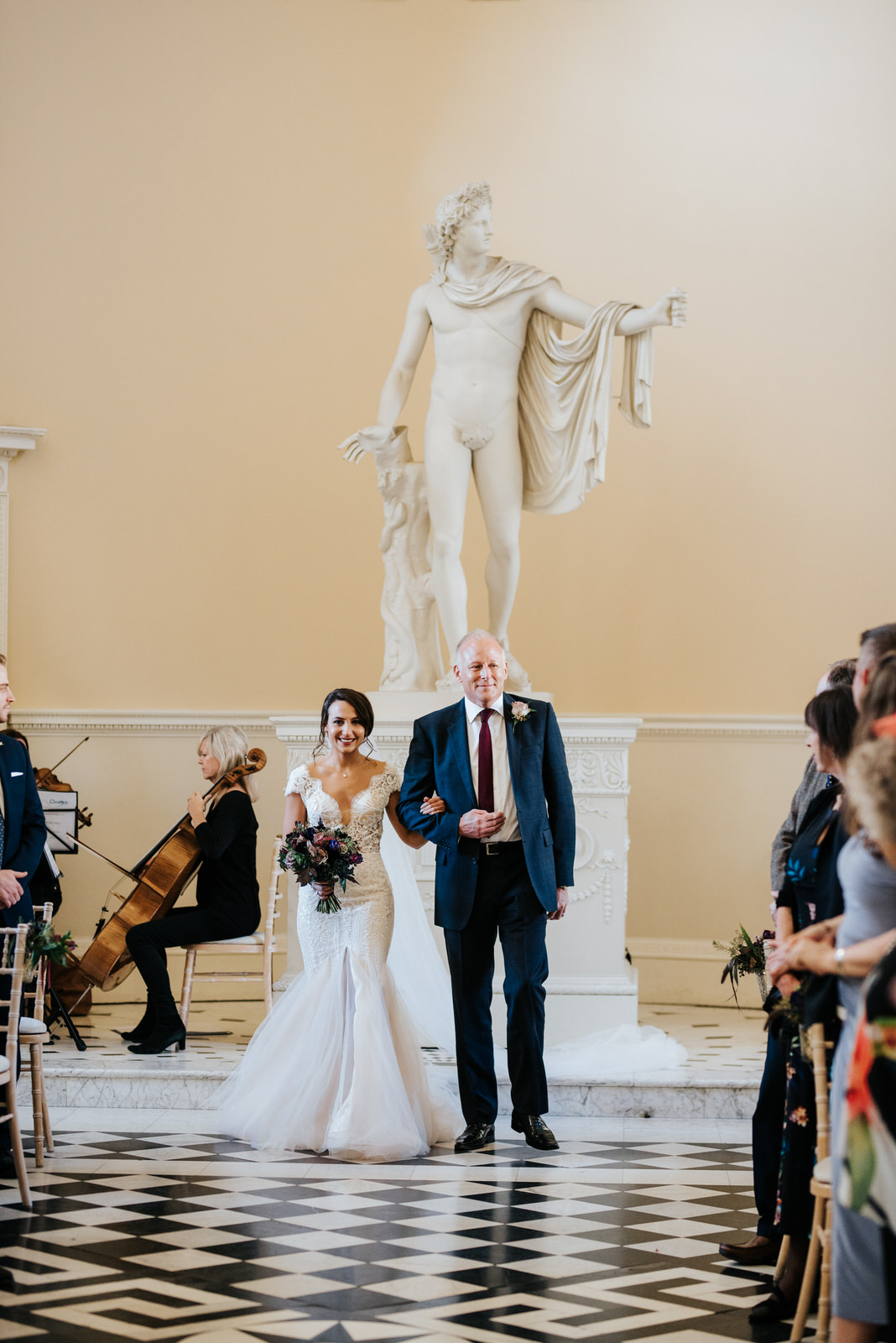 Bride and step-dad walk down the aisle as people smile