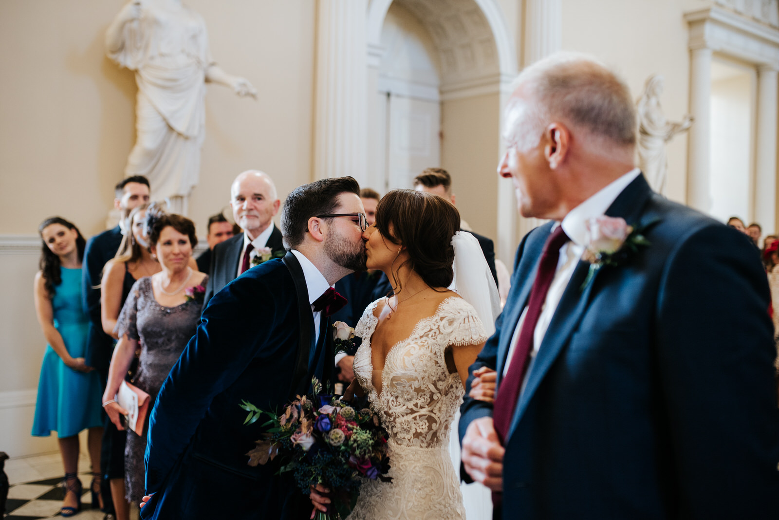 Bride and groom see each other at the front of the aisle and kiss