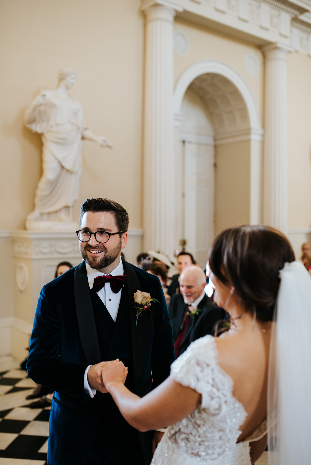 Groom smiles as he holds bride's hand while repeating wedding vows