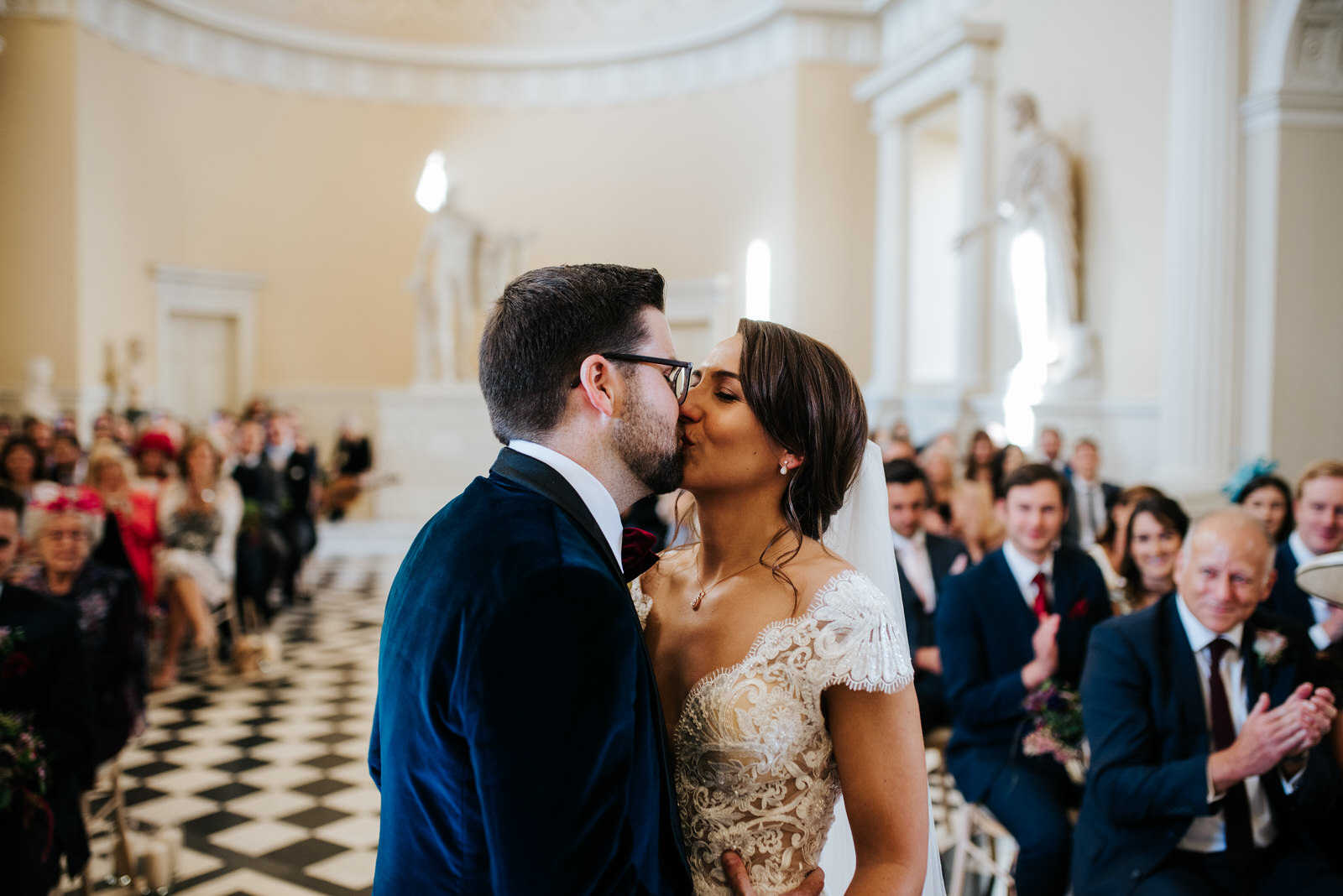 Bride and groom share their first kiss during ceremony at Syon House as guests look from back