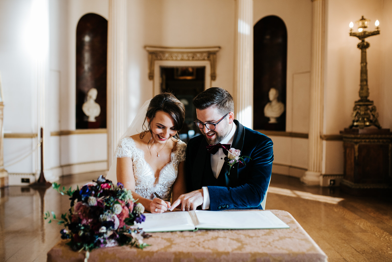 Bride and groom look extremely happy as they sit and sign wedding register