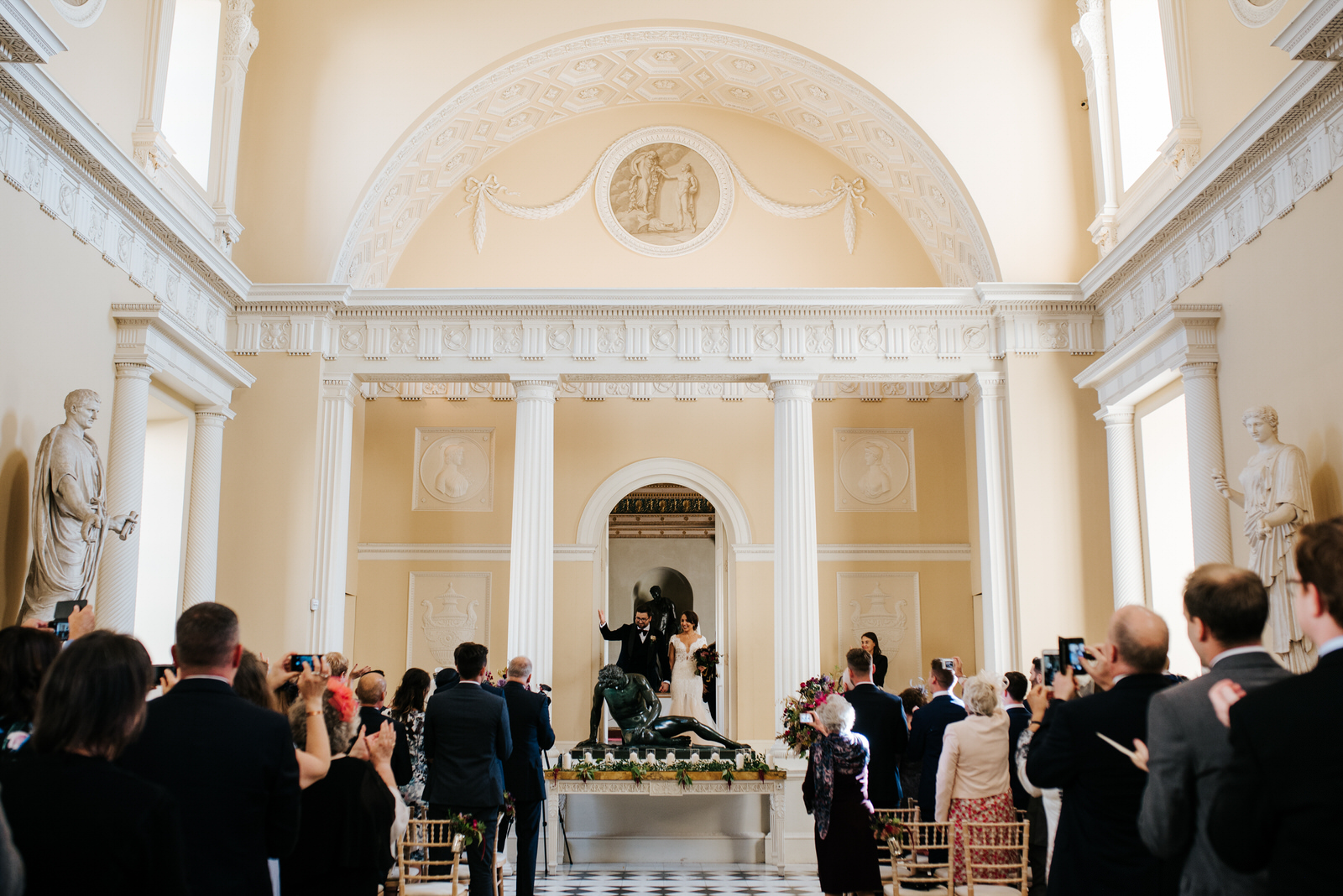 Bride and groom walk out of door flanked by stunning arches and statues as they are announced as husband and wife Syon House