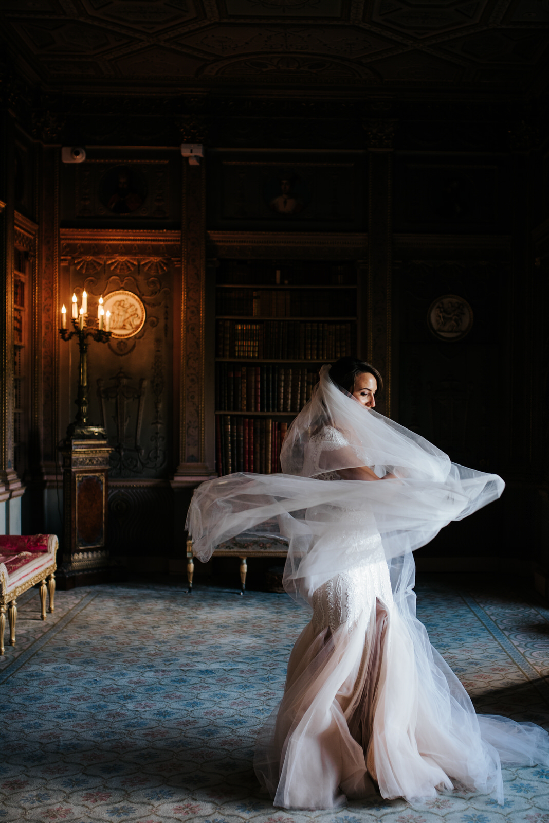 Bride twirls in her stunning dress and veil as light comes in from window