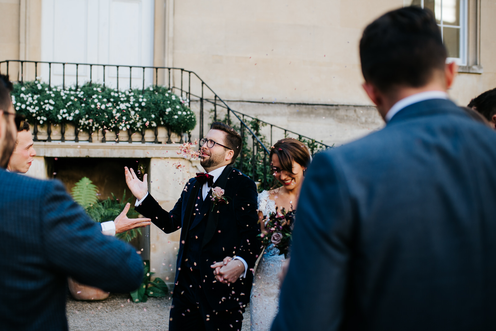 Guests throw confetti as couple walks in front of them