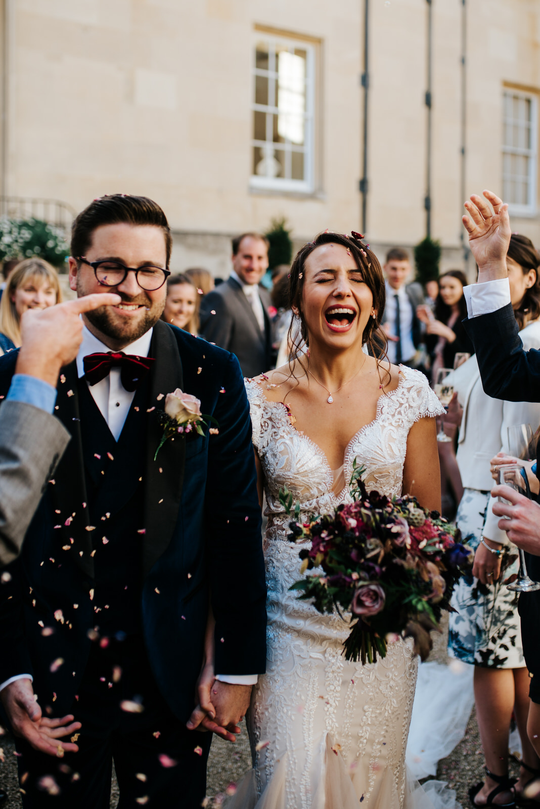 Bride and groom pull funny faces as confetti is thrown at them after wedding ceremony