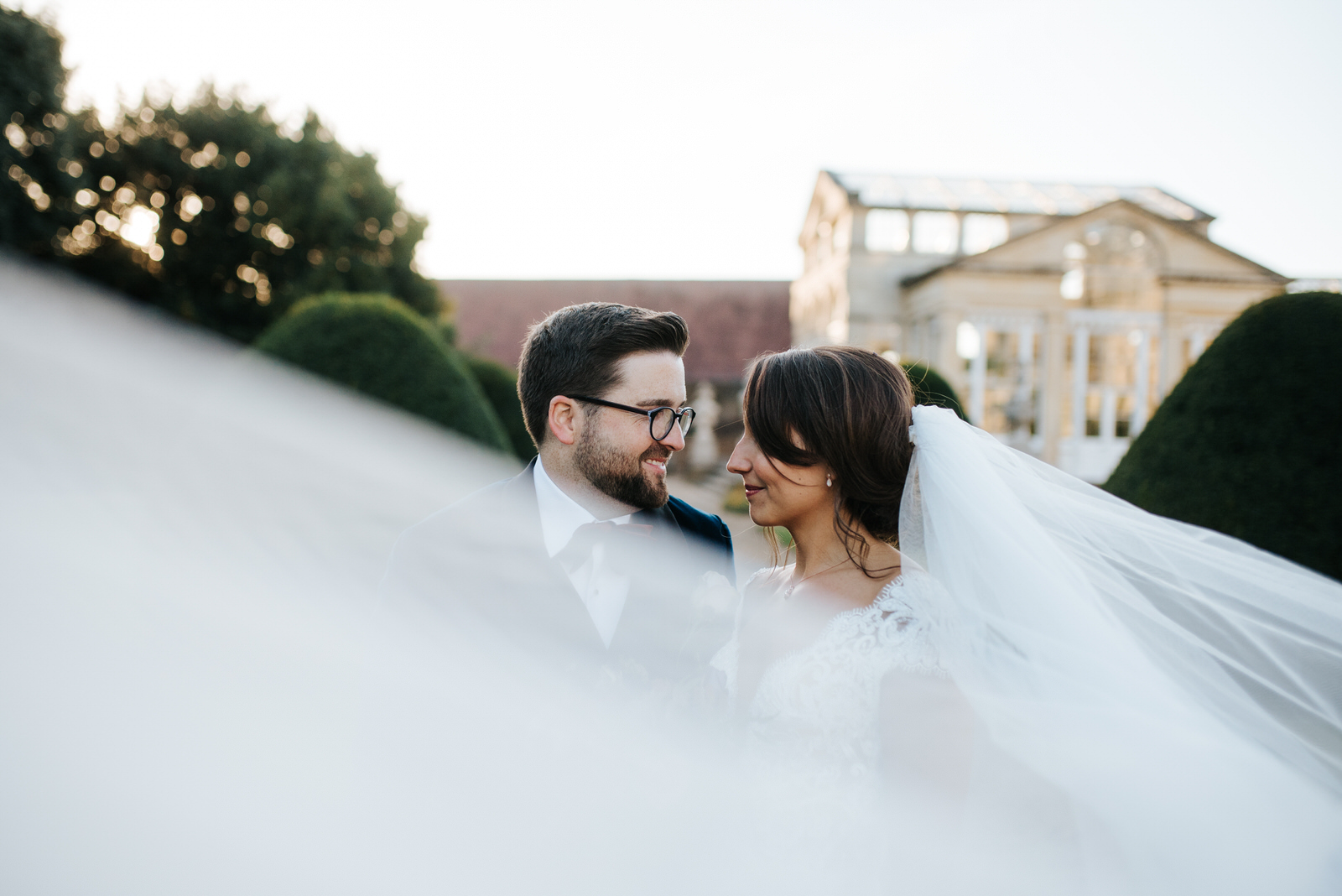 Romantic photo of bride and groom looking at each other while her veil floats in front of camera