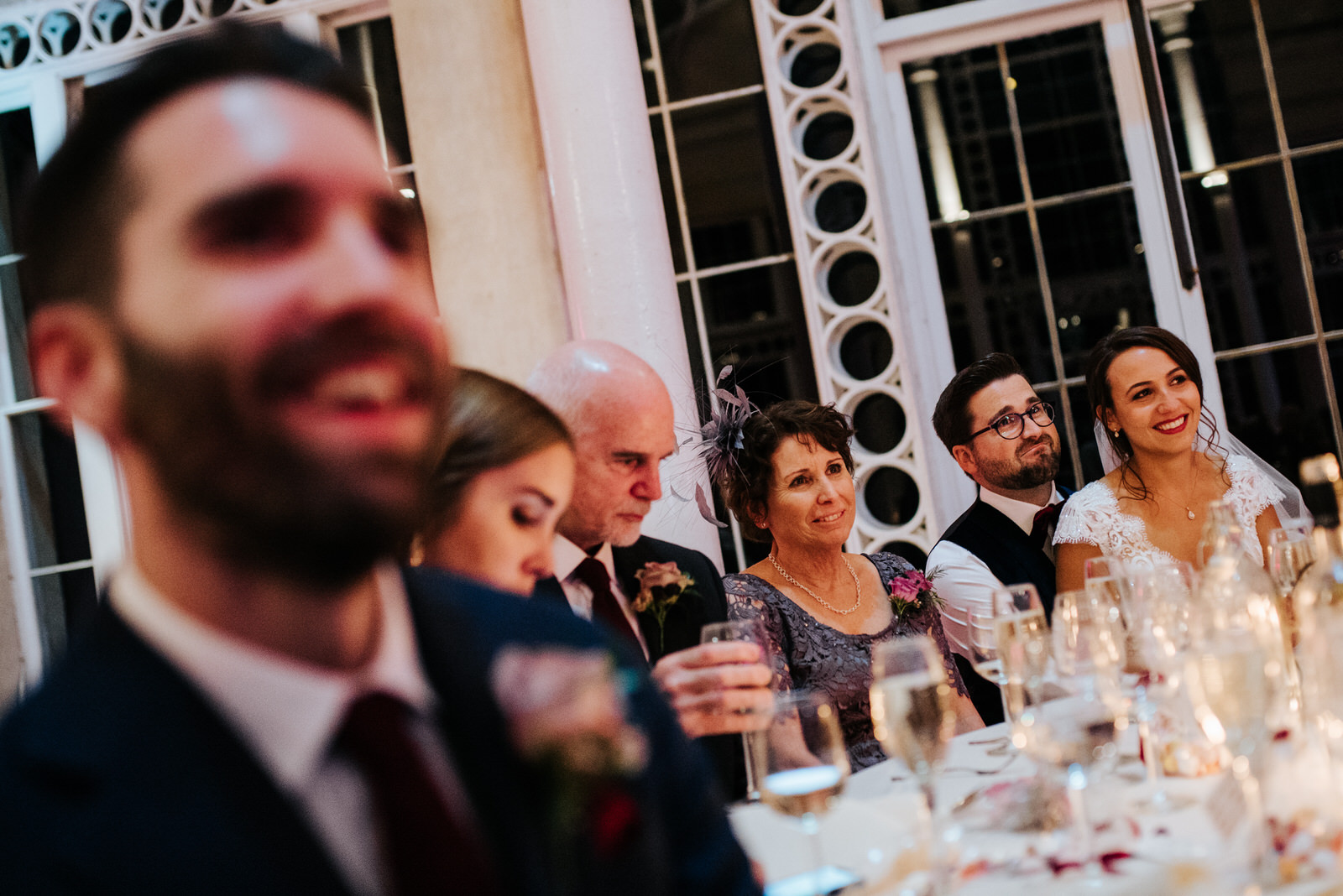 Photograph of bride, groom and family listening to wedding speeches