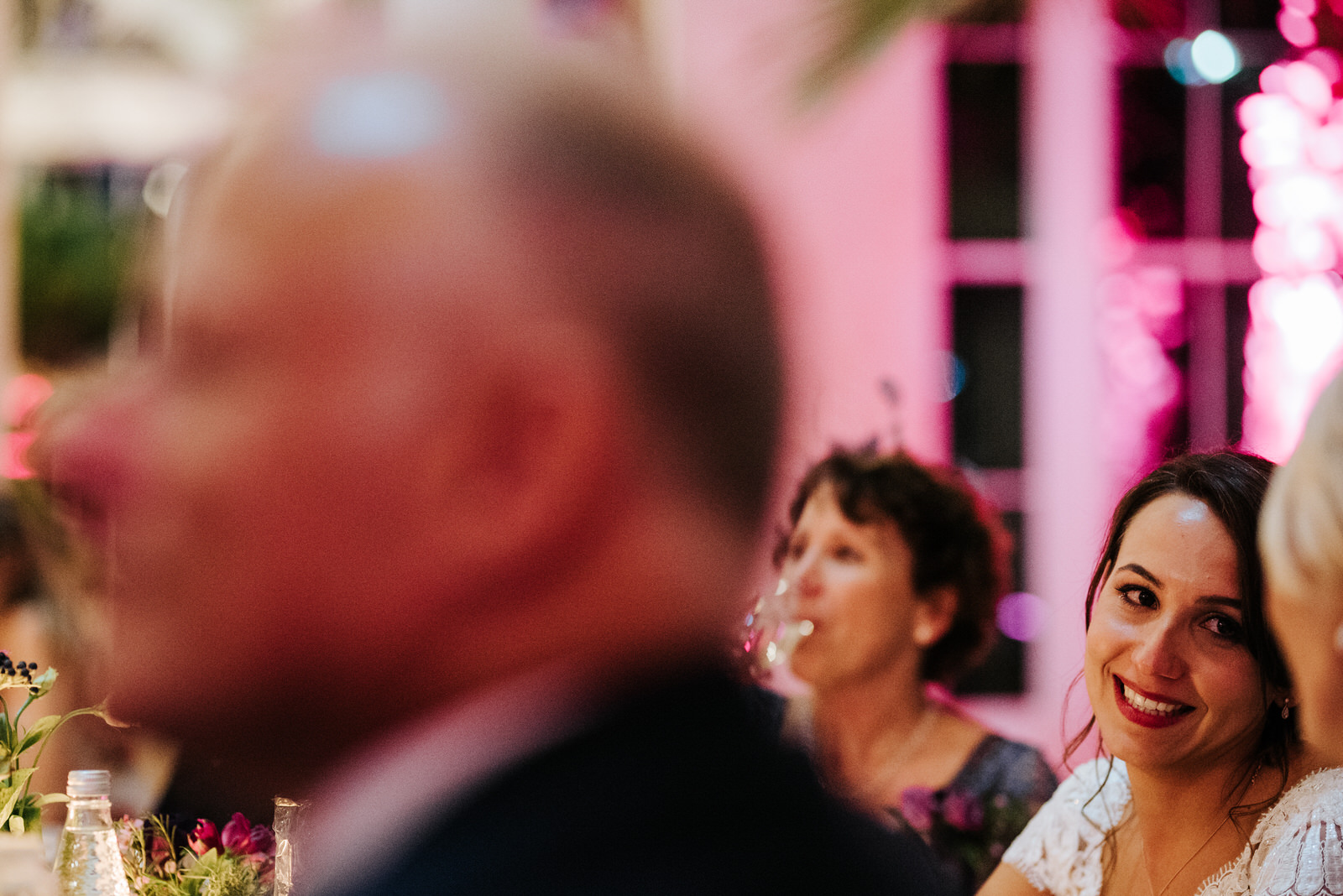 Bride looks at her mum and smiles during her husband's wedding speech