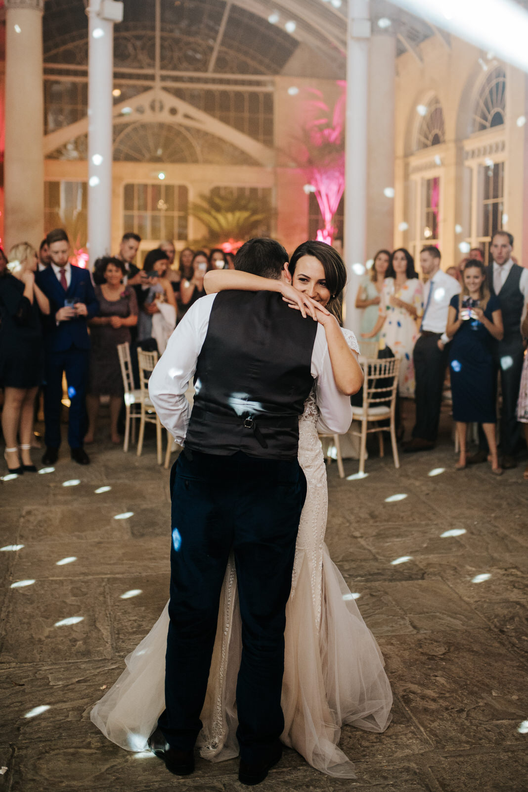 Bride hugs groom as they begin their first dance, flanked by guests