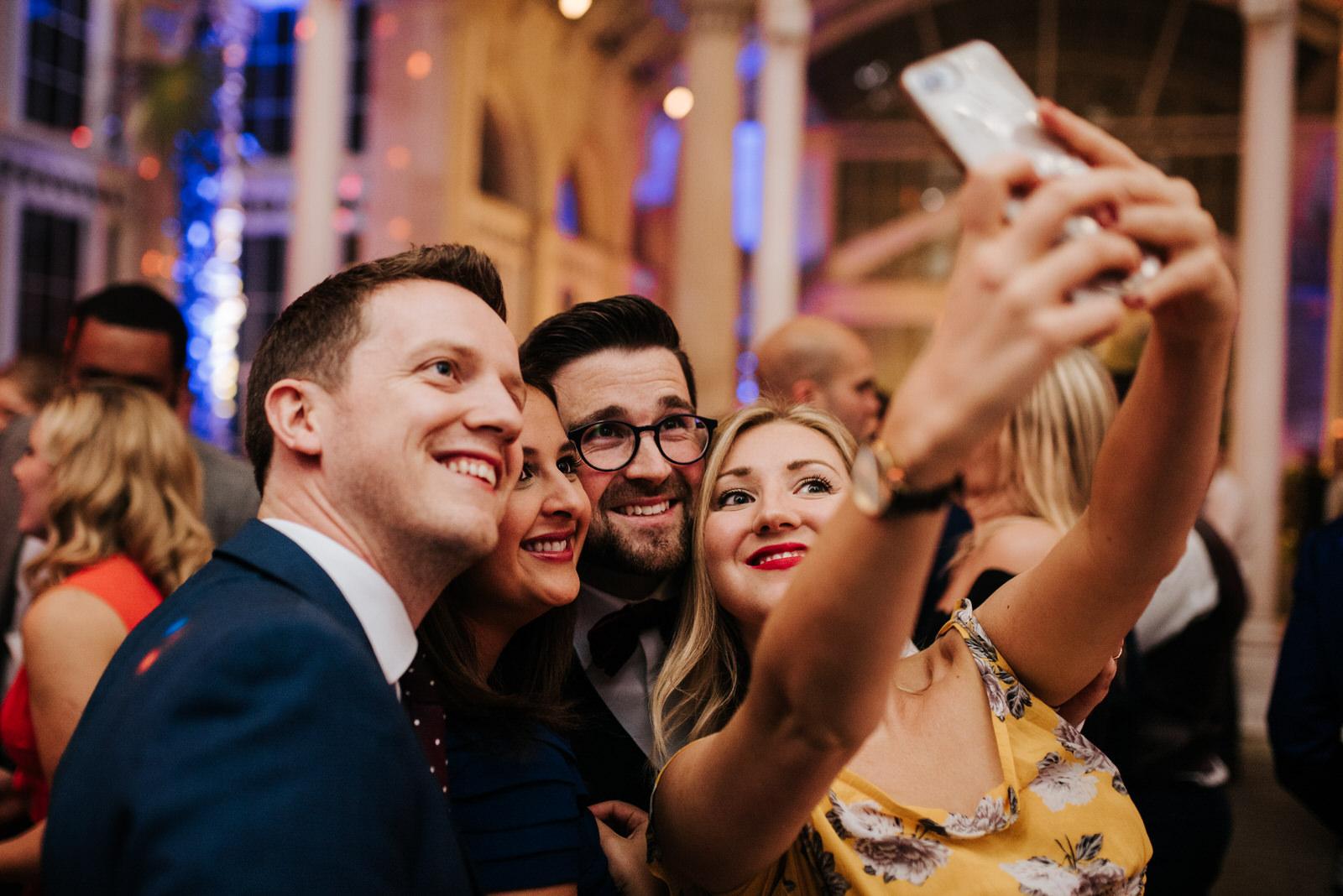 Guests take wedding selfie with groom