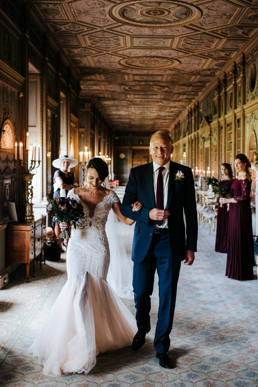 Bride and step-dad walk towards the aisle as mum and bridesmaids look joyfully from behind