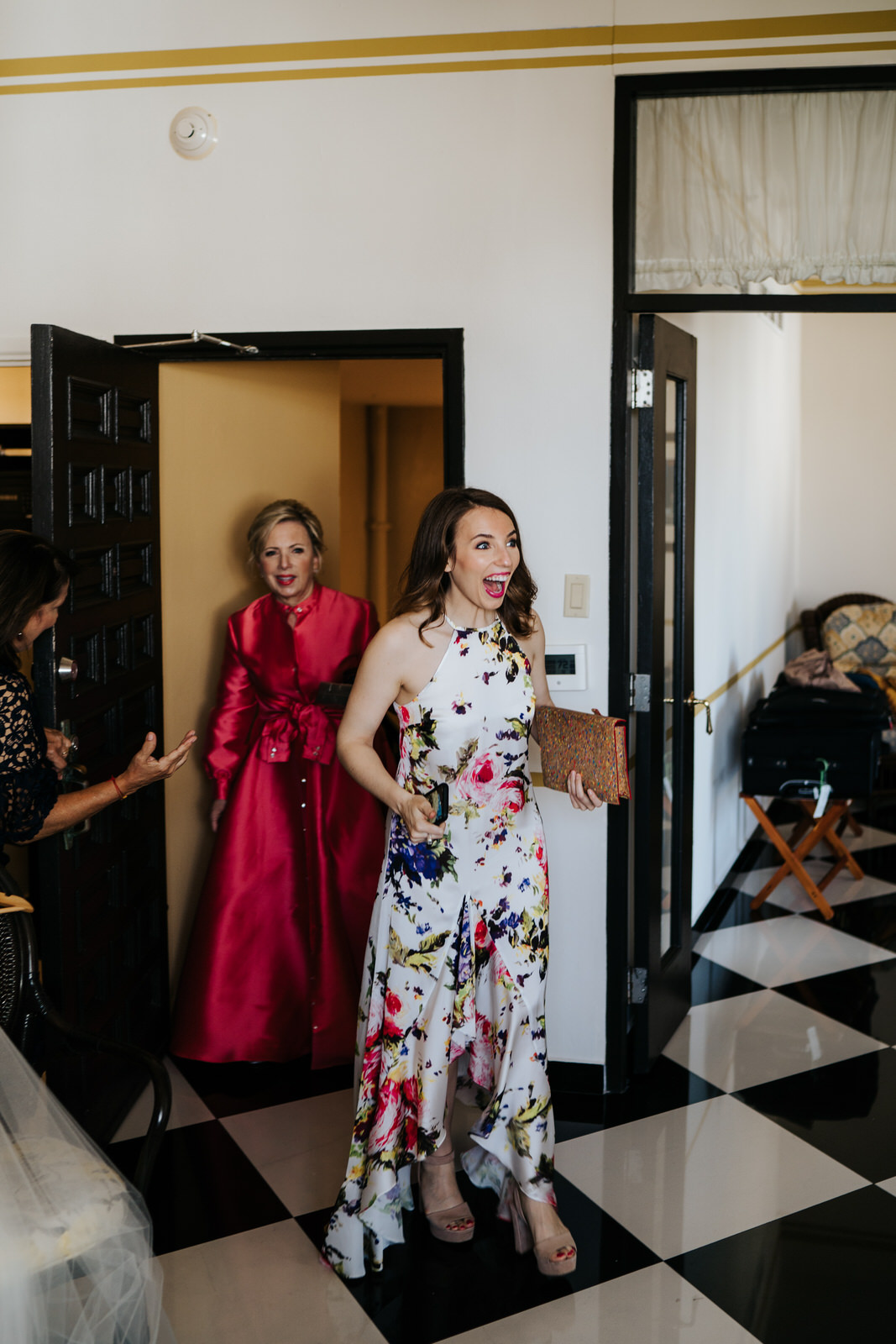 Groom's sister and mother enter the room where bride is getting ready for wedding and smile in shock when they see her