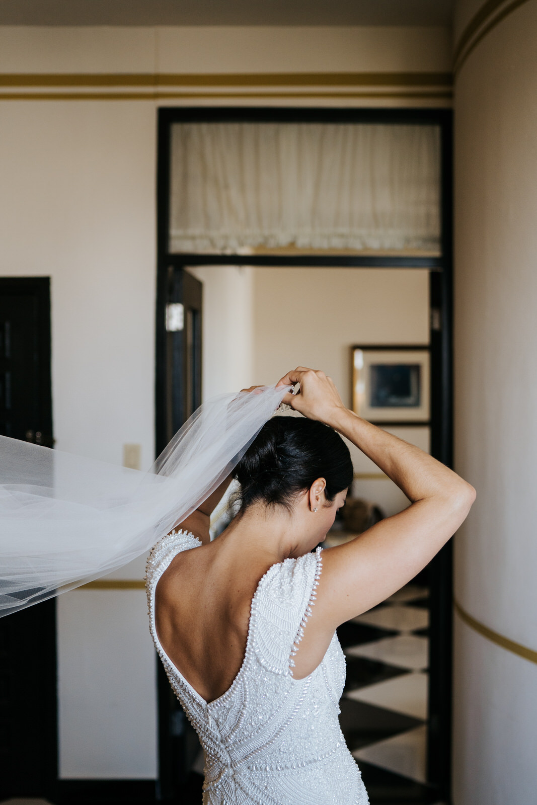 Bride, in her dress, puts on veil in hotel room