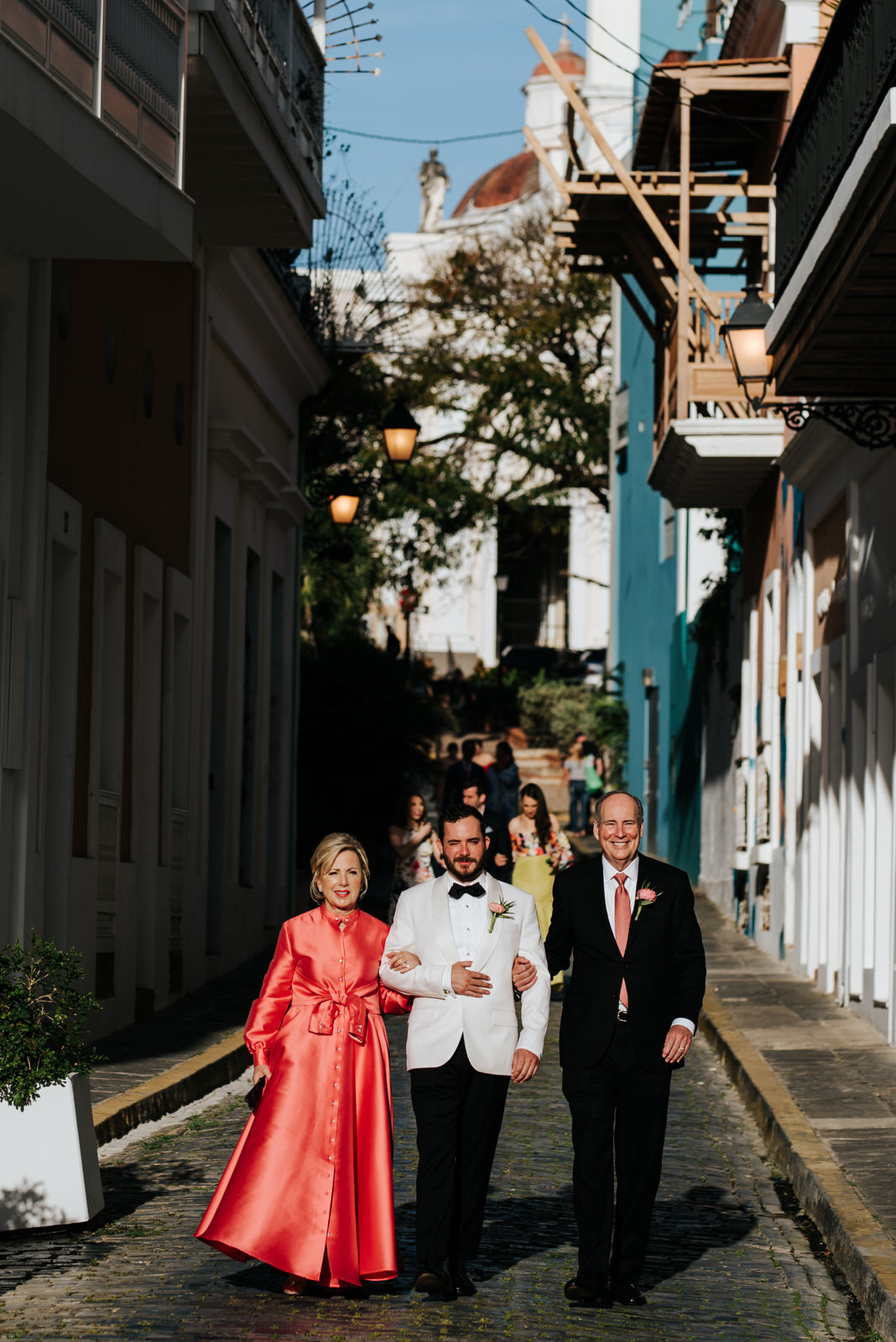 Groom and his parents walk down the streets of old san juan towards the wedding aisle