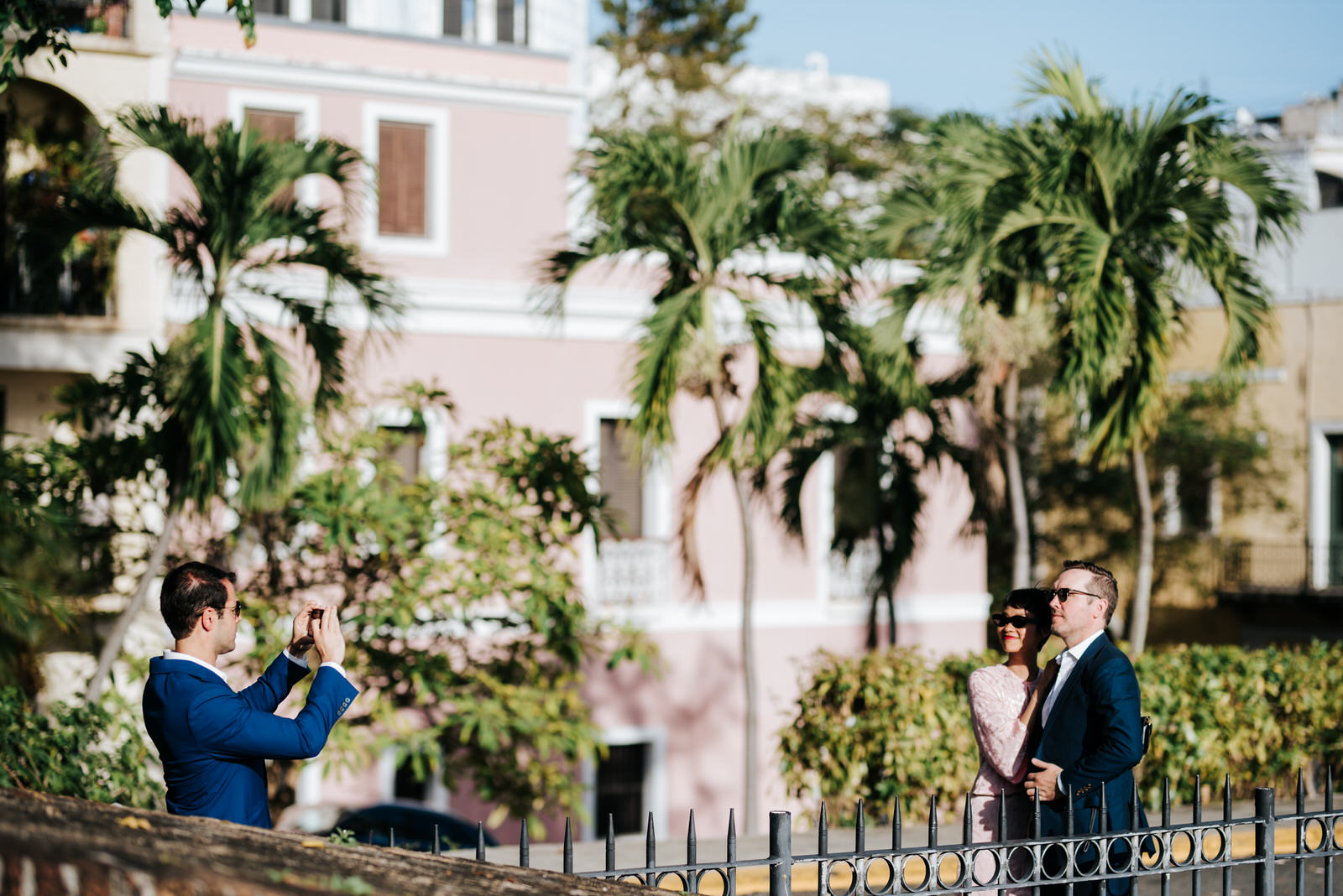 Guests take photos next to ceremony spot in Old San Juan while sun shines on the palm trees in the background