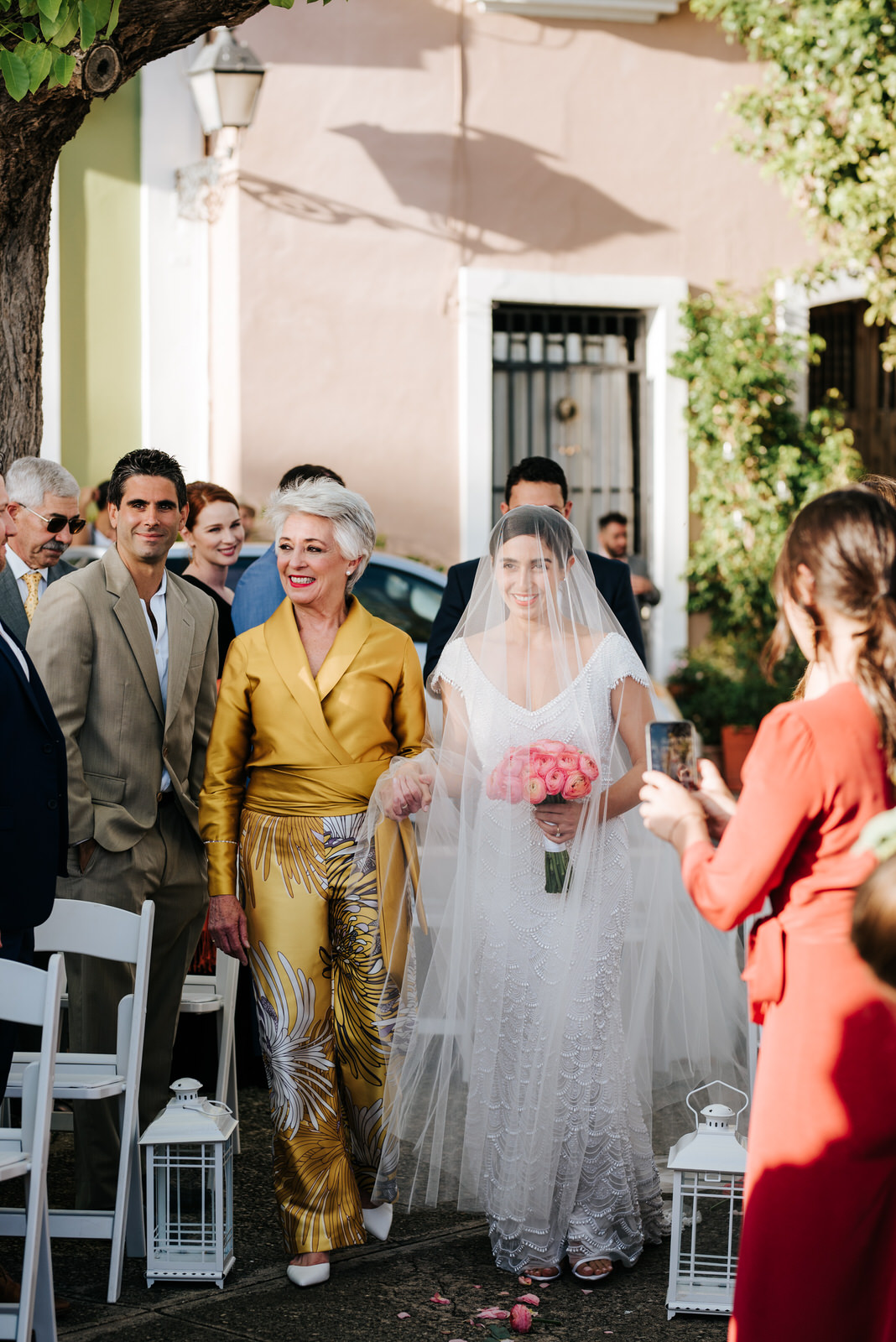 Bride and her mother walk down the wedding aisle as they smile and exchange glances with guests during this wedding in Old San Juan Puerto Rico