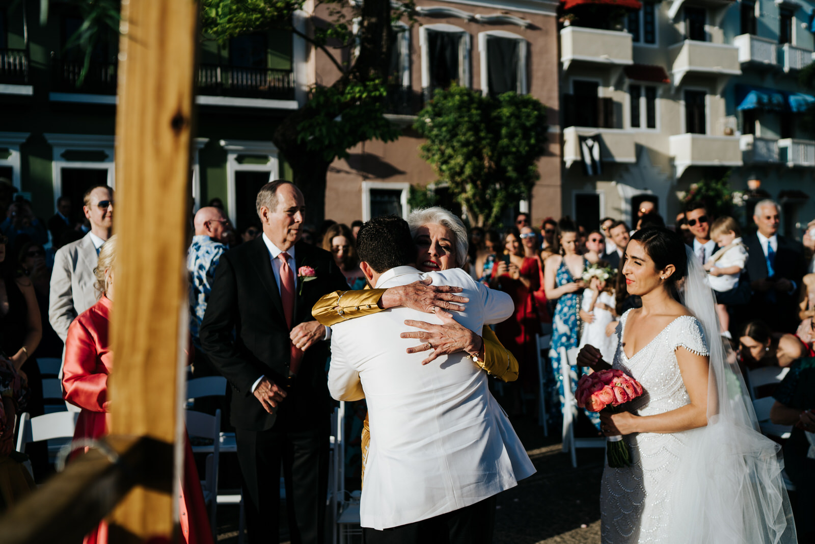 Bride's mother embraces the groom after reaching the front of the aisle