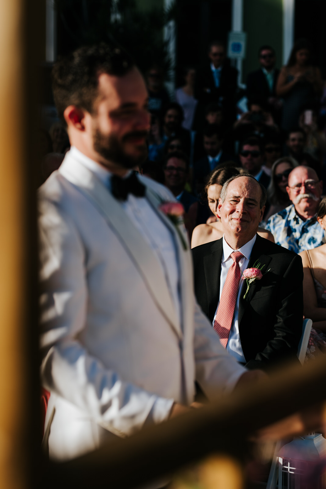 Groom stands, out of focus, at the front of the aisle as his father smiles towards him from the background