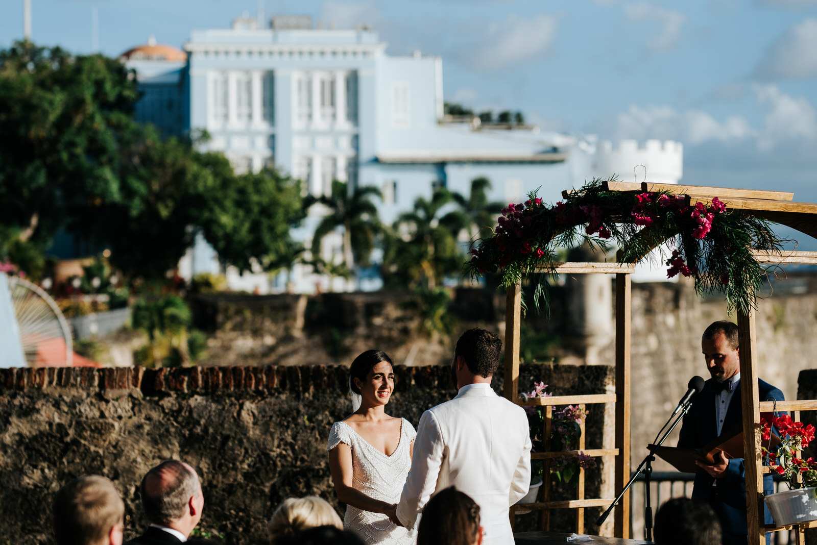 Wide photograph of where the wedding ceremony took place at La Rogativa in Old San Juan, Puerto Rico with the bride and groom holding hands and smiling at the front and La Fortaleza in the back